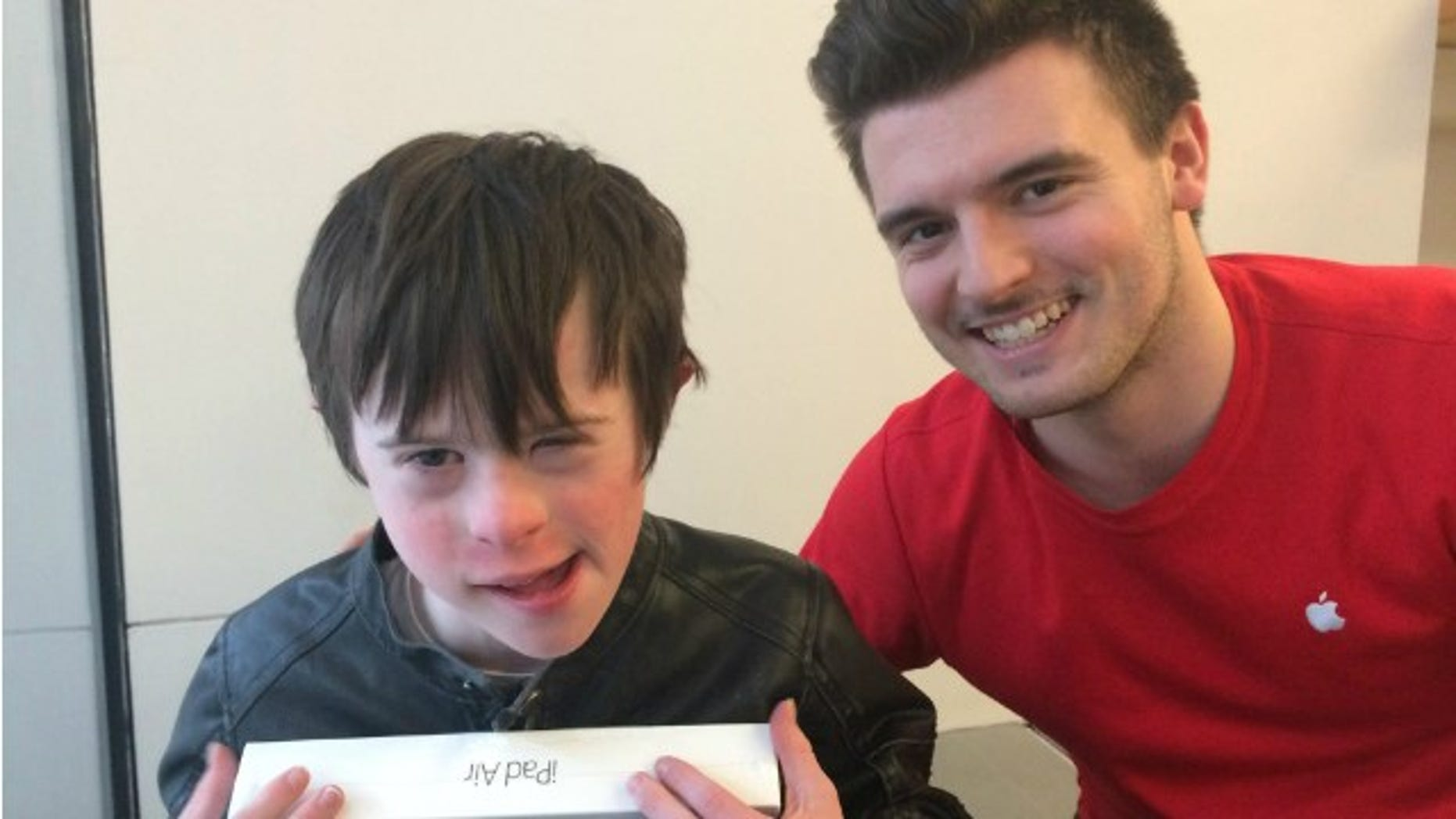 James Rink, 9, poses with Apple Store employee Andrew Wall. Wall helped Rink set up his new iPad on the floor after Rink accidentally ran into a glass wall and fell.