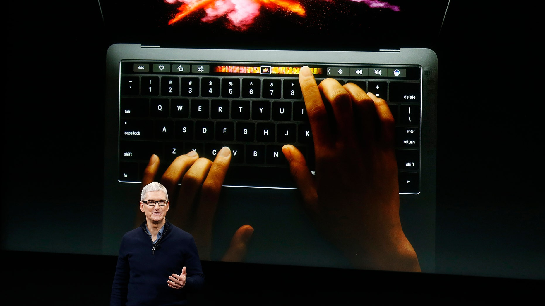 Apple CEO Tim Cook speaks under a graphic of the new MacBook Pro during an Apple media event in Cupertino, California, U.S. Oct. 27, 2016. (REUTERS/Beck Diefenbach)