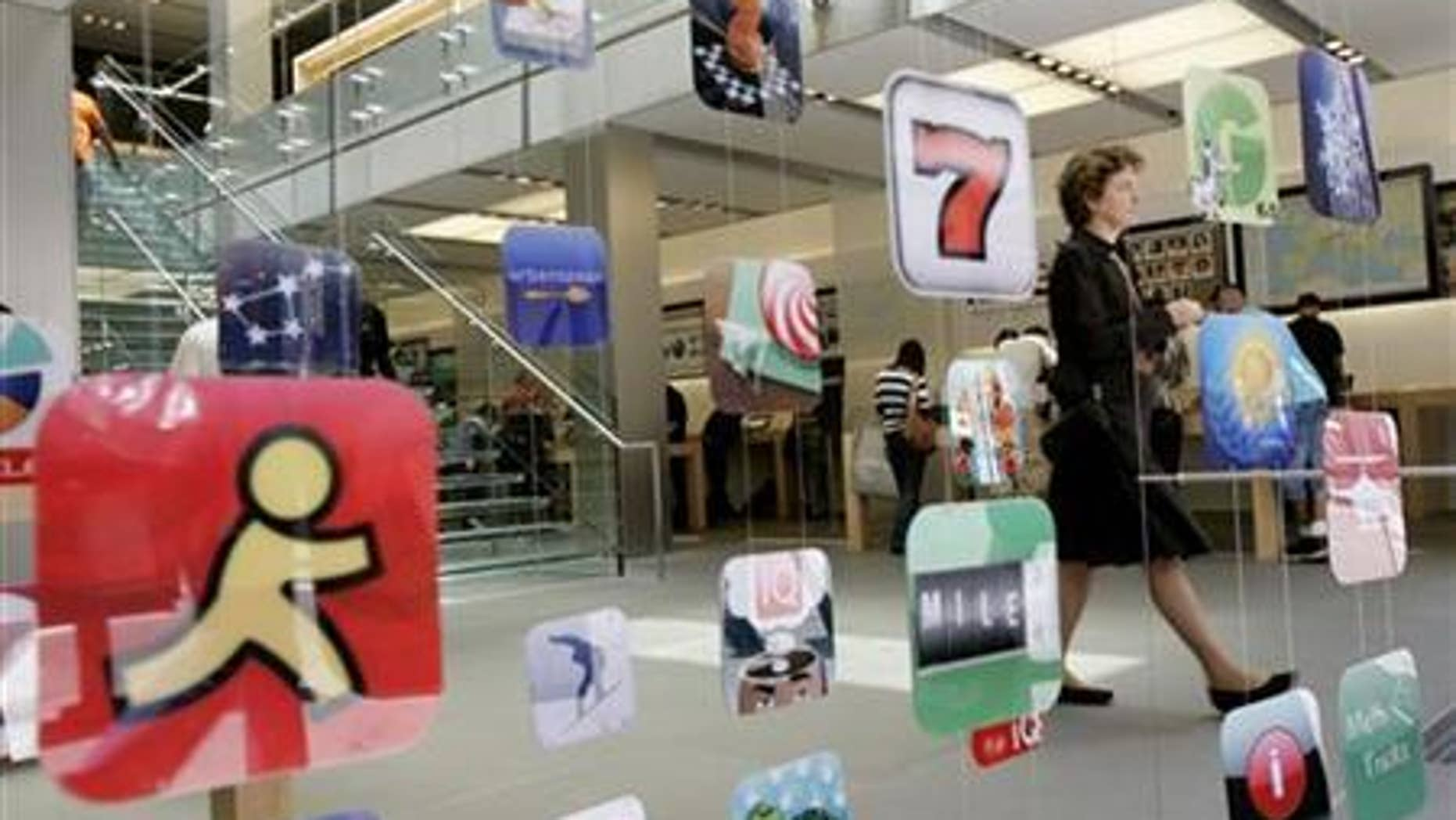A woman walks past icons for Apple applications at the company's retail store in San Francisco, California.