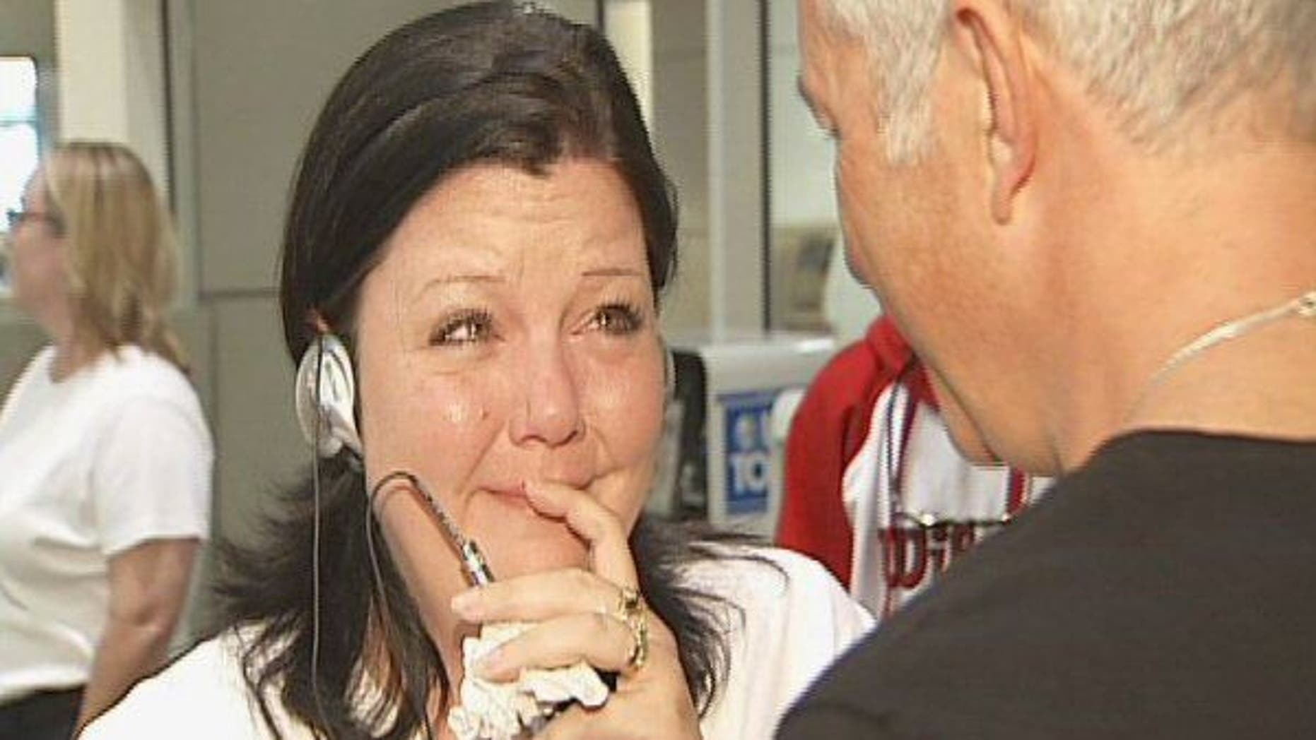 April Beaver listens to her deceased son Caleb's heart, beating in donor recipient Chuck Shelton's chest, through a stethoscope.