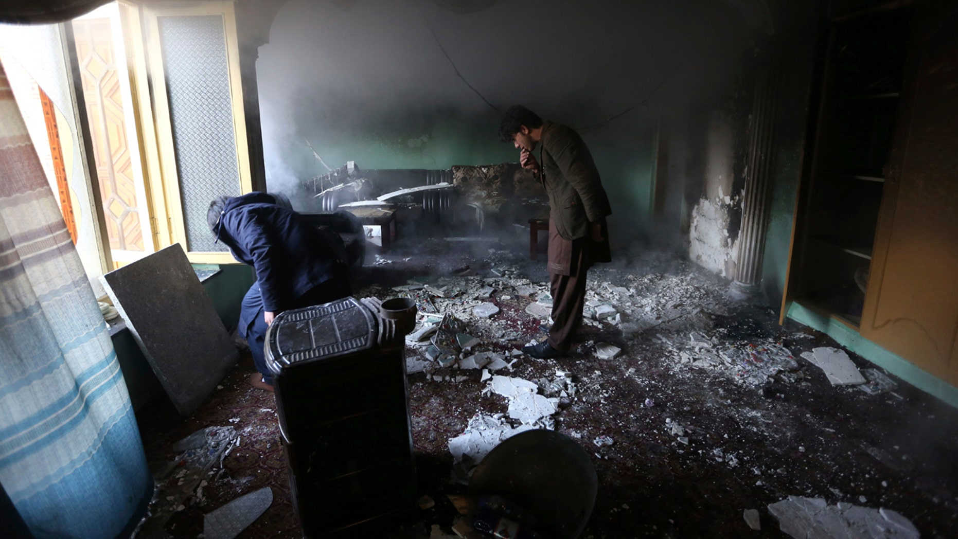 Afghan men inspect the remains of their belongings at the house of parliament member Mir Wali in the aftermath of gunmen's attack late Wednesday in western Kabul, Afghanistan, Thursday, Dec. 22, 2016.