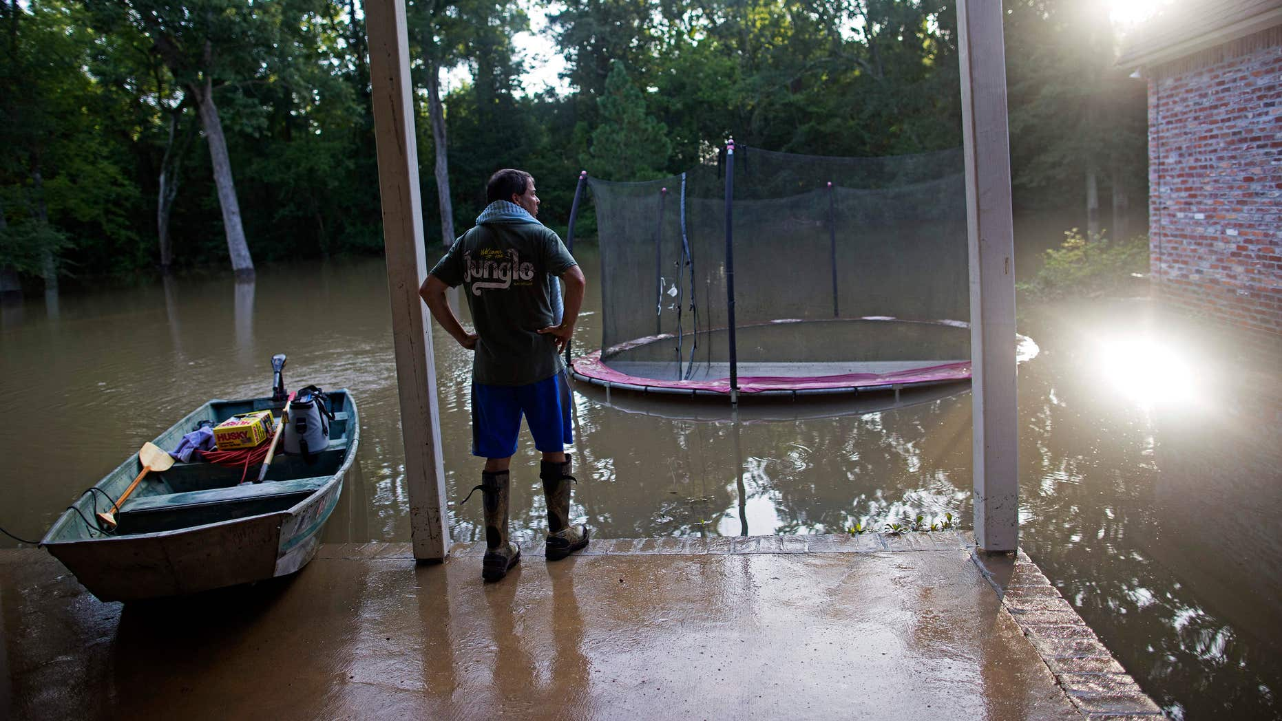 David Key looks at the back yard of his flooded home in Prairieville.