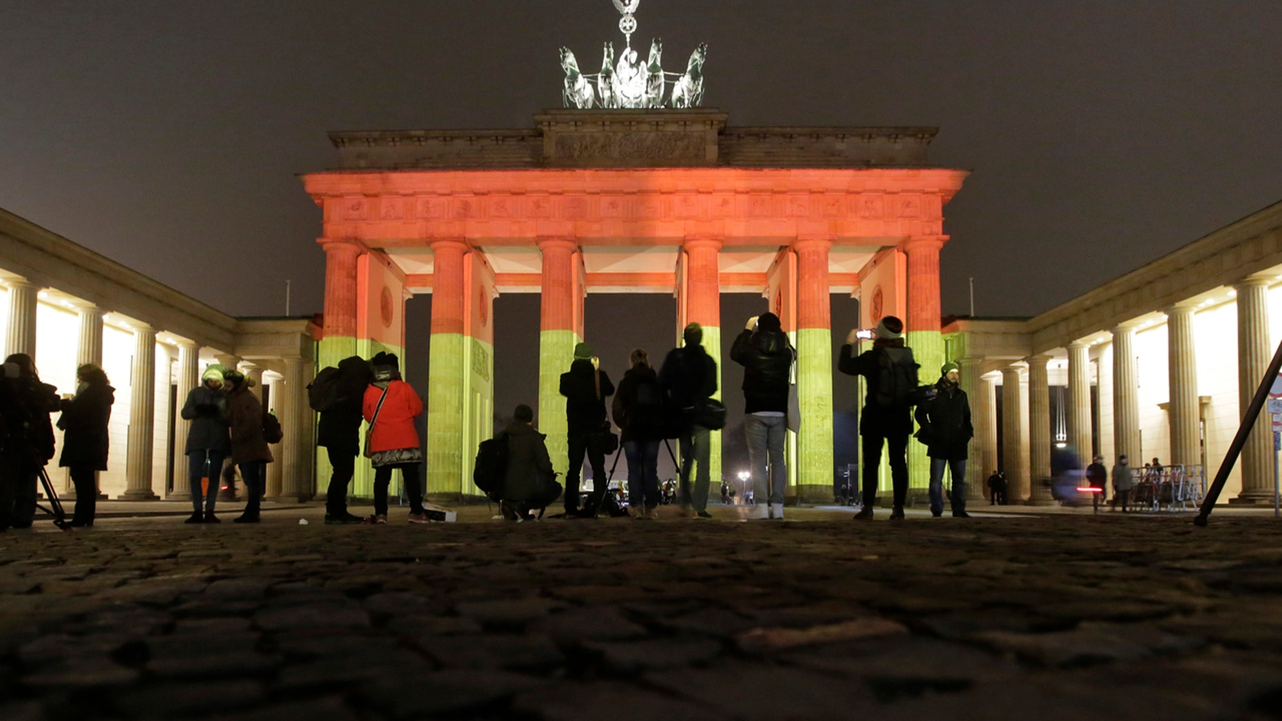 The Brandenburg Gate is illuminated in the colors of the German flag in Berlin, Germany, Tuesday, Dec. 20, 2016, the day after a truck ran into a crowded Christmas market and killed several people. (AP Photo/Markus Schreiber)