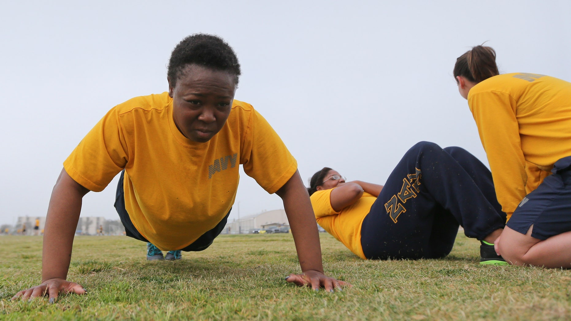 Petty Officer Lentoyi White does pushups while training with fellow Petty Officer Theresa White Monday, Feb. 29, 2016, in Coronado, Calif. The pair are trying to lose weight and improve their fitness in order to pass the Navy fitness test and avert being discharged. (AP Photo/Lenny Ignelzi)