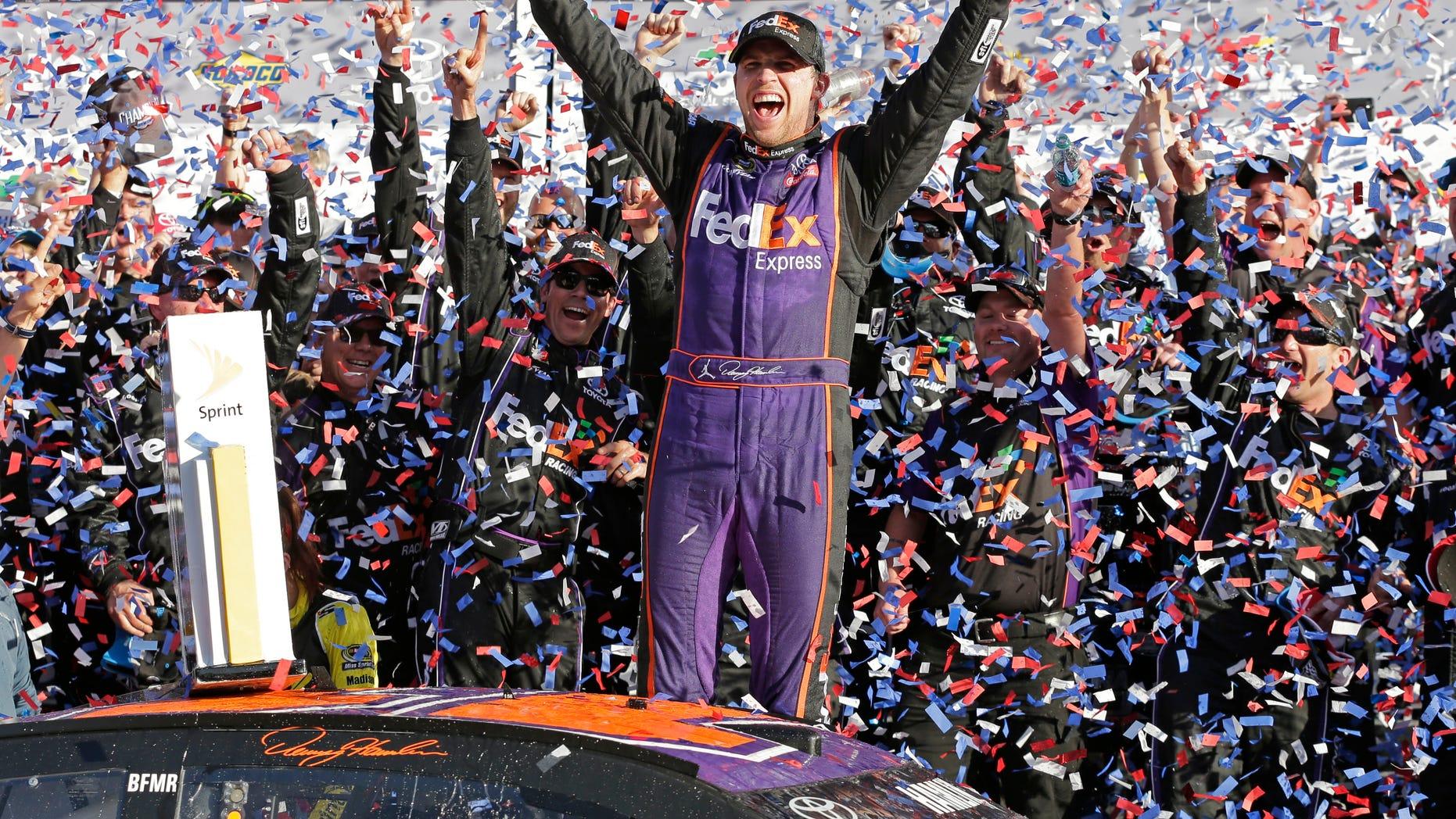 Denny Hamlin celebrates in Victory Lane after winning the NASCAR Daytona 500 Sprint Cup Series auto race.