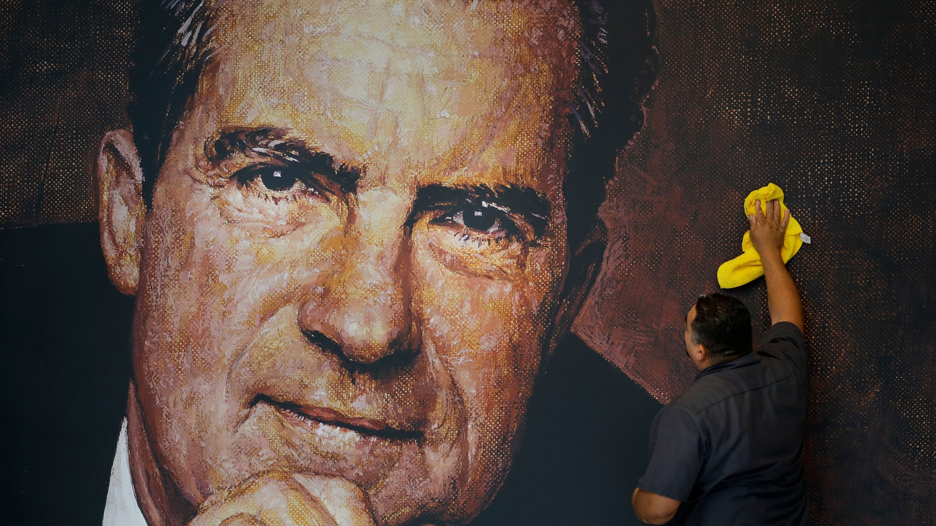 Oct. 5, 2016: Tayron Santos cleans the newly-installed wall mural of former President Richard Nixon in the lobby area of the Richard Nixon Presidential Library and Museum in Yorba Linda, Calif.
