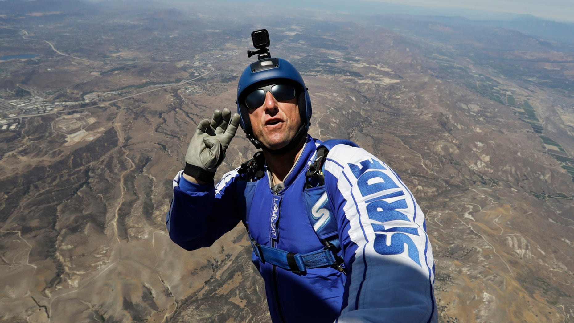 July 25, 2016: Skydiver Luke Aikins signals to pilot Aaron Fitzgerald as he prepares to jump from a helicopter in Simi Valley, Calif.
