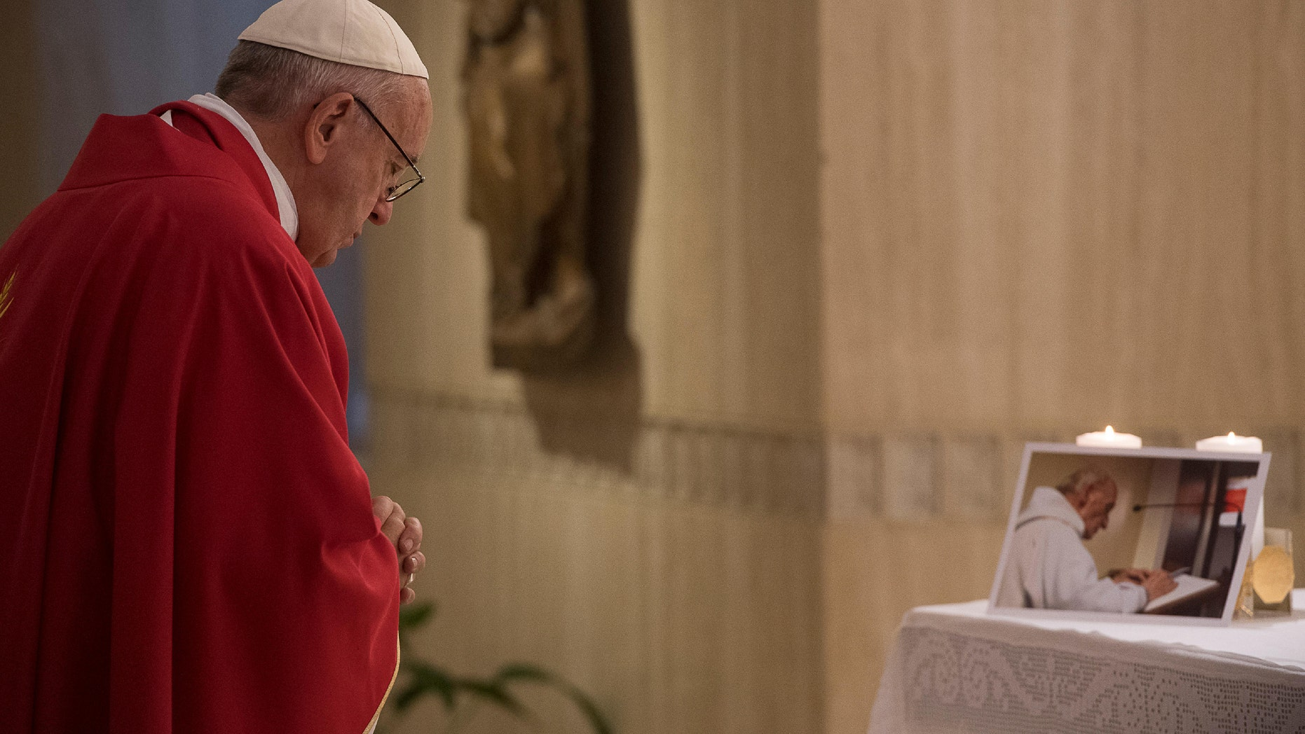 Pope Francis prays in front of a picture of Rev. Jacques Hamel on Wednesday.