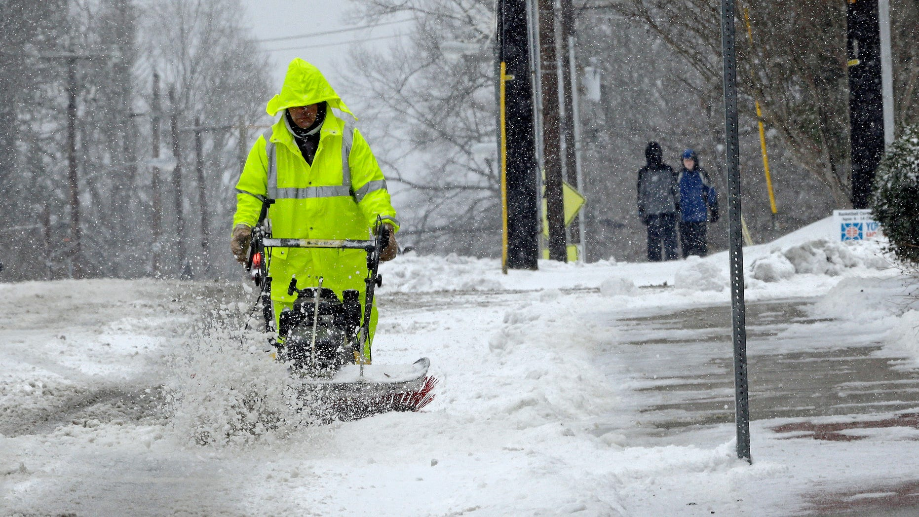 A city worker removes snow from a crosswalk as a winter storm blankets the area in Carrboro, N.C., Saturday, Jan. 7, 2017.   Snow and sleet pounded a large swath of the East Coast on Saturday, coating roads with ice and causing hundreds of crashes  (AP Photo/Gerry Broome)