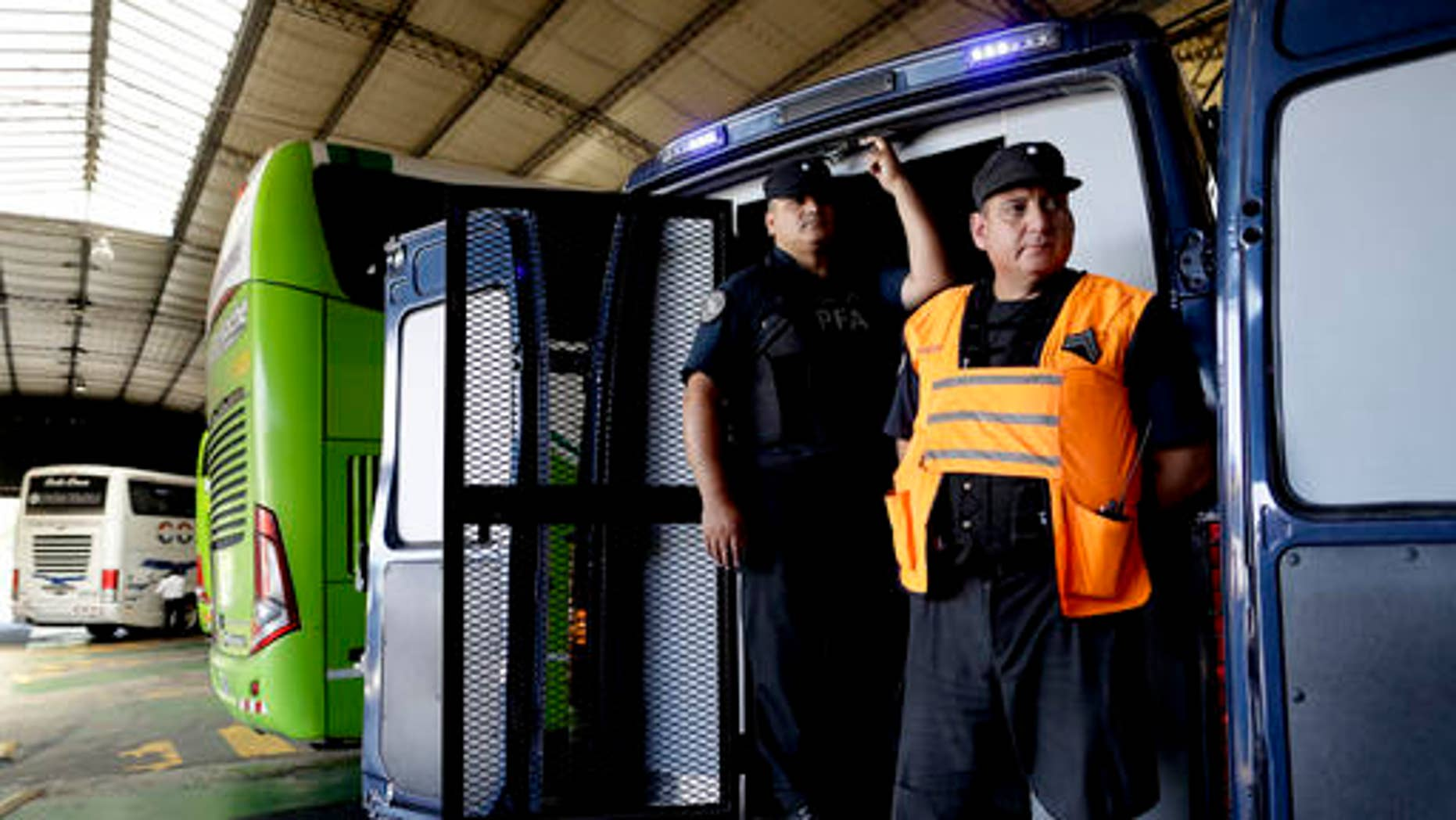 Police guard vehicle holding bags confiscated at a bus station on the outskirts of Buenos Aires, Jan. 27, 2017