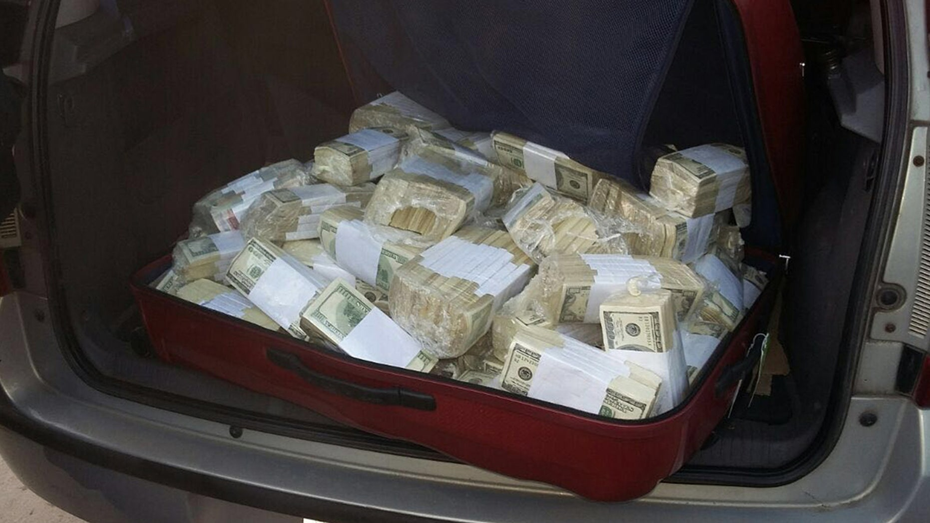 June 14, 2016:  In this photo released by the Buenos Aires Province Security Ministry, wads of cash sit in the back of a vehicle shortly after former Public Works Secretary Jose Lopez was caught by police hiding millions at a monastery in the outskirts of Buenos Aires