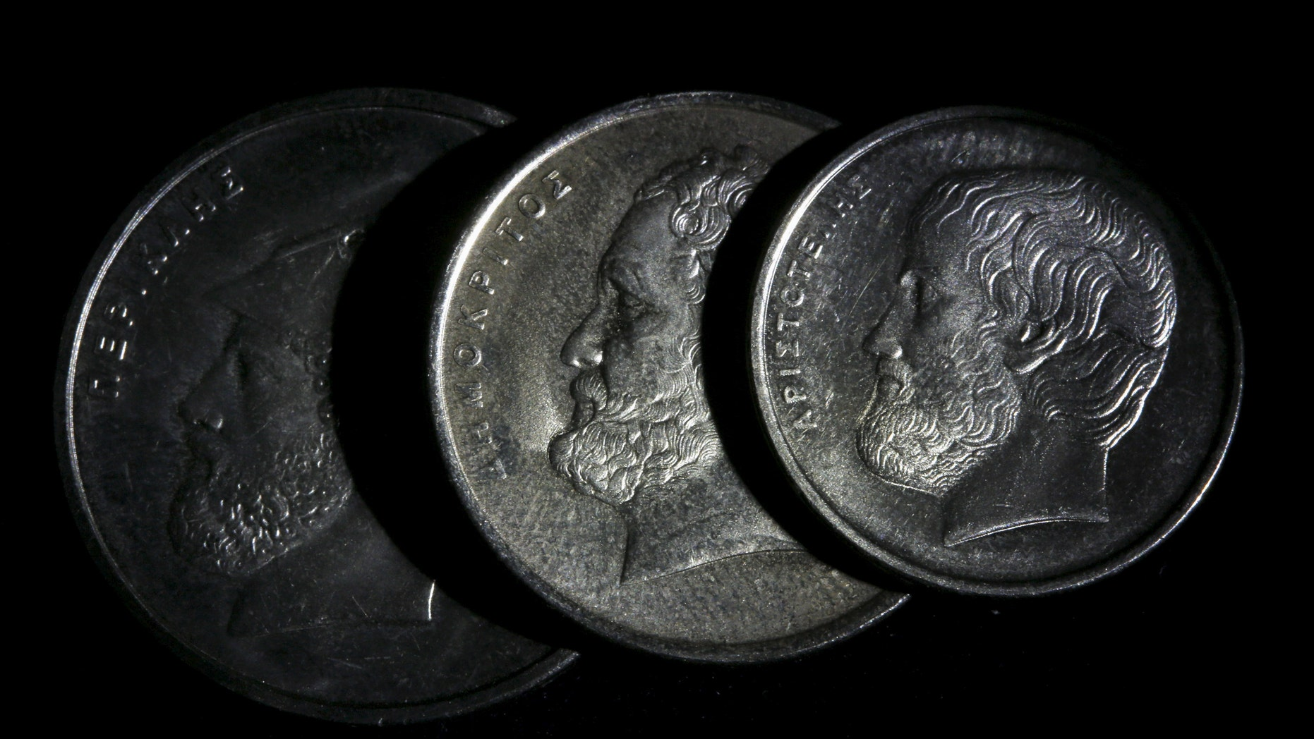 File photo - Ancient Greek philosopher Aristotle (L), philosopher and scientist Democritus (C) and Athenian politician and general Pericles are depicted on Greek Drachma coins in this picture illustration taken in Athens March 22, 2015. (REUTERS/Yannis Behrakis)