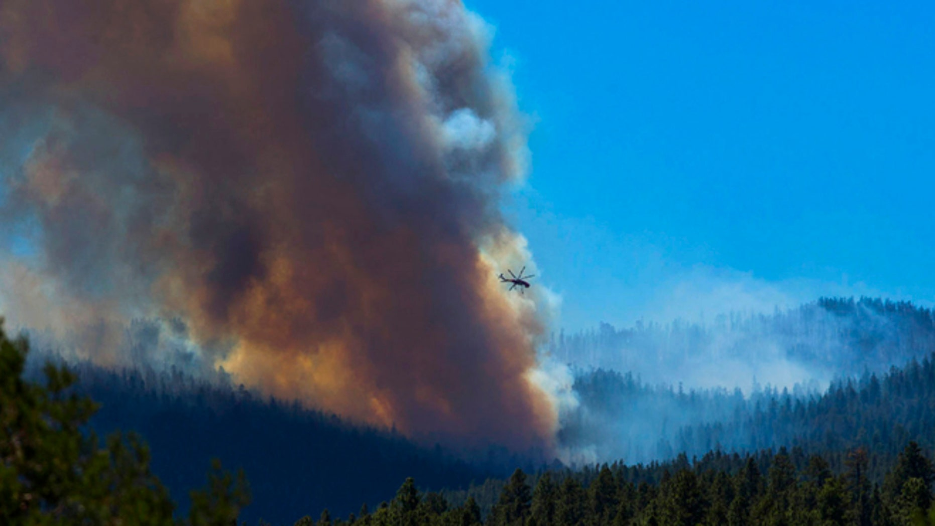 June 27, 2014: A helicopter battles the blaze with lake water as smoke rises from the trees of the San Juan fire near Vernon, Ariz.