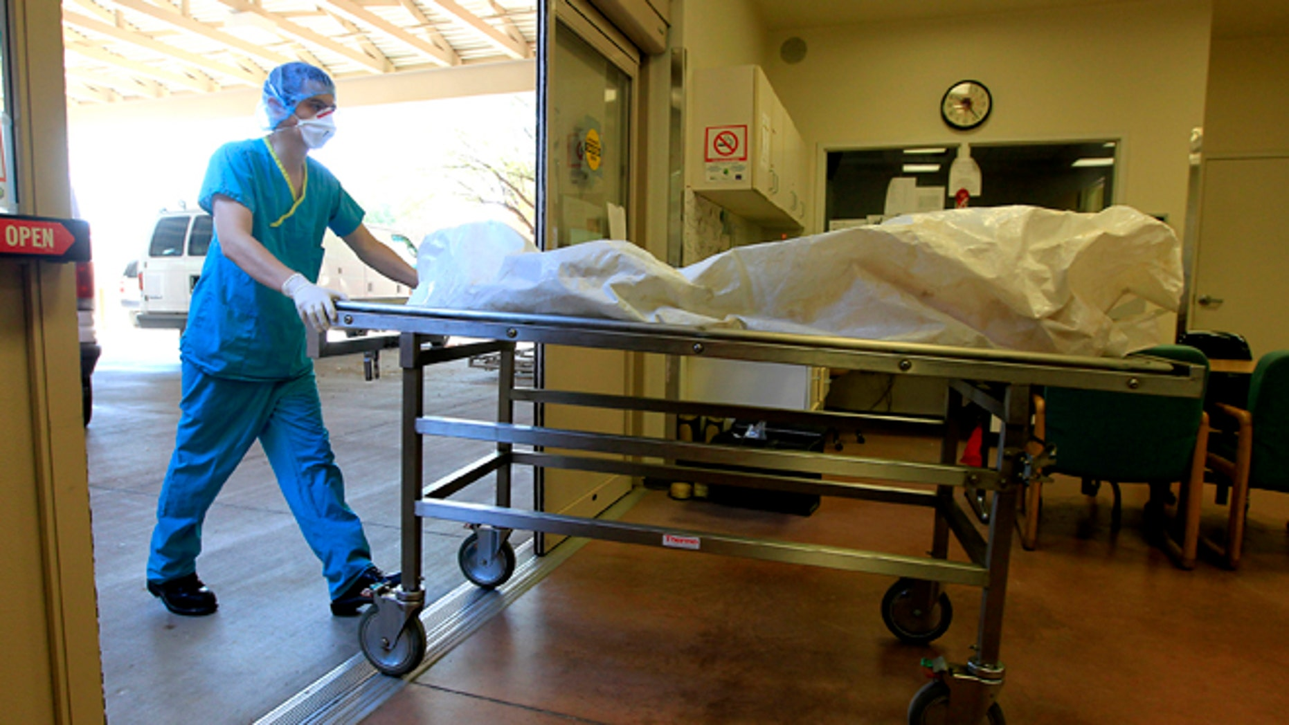 Aug. 10, 2012: In this photo, a morgue staff member brings in the body of a suspected illegal immigrant found in the Arizona desert, at the Pima County morgue in Tucson, Ariz.