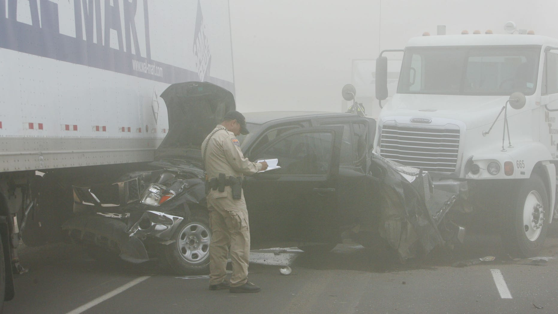 Oct. 4: An Arizona Departmaent of Public Safety Highway Patrol officer investigates the scene of a pileup caused by a dust storm on Interstate 10 west of Casa Grande, Ariz. A blinding dust storm rolled across the Arizona desert Tuesday, causing three pileups involving dozens of vehicles on the major interstate. One man was killed and at least 15 other people were injured, authorities said.