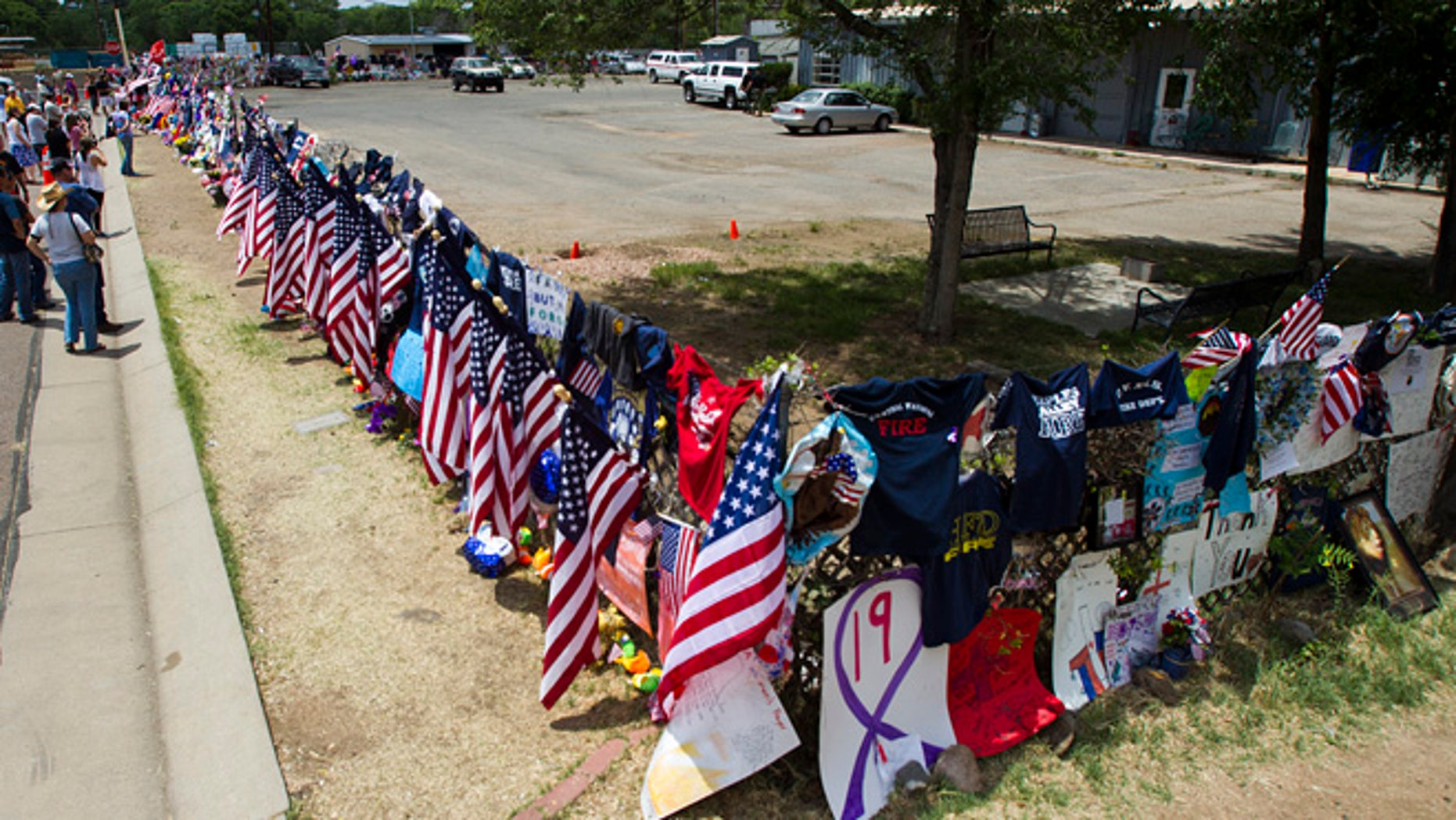 July 6, 2013: Items are displayed at a makeshift memorial at the Fire Station No. 7 memorial for fallen firefighters Saturday, July 6, 2013, in Prescott, Ariz. Nineteen Granite Mountain Hotshot firefighters were killed by an out-of-control blaze near Yarnell, Ariz. on June 30.