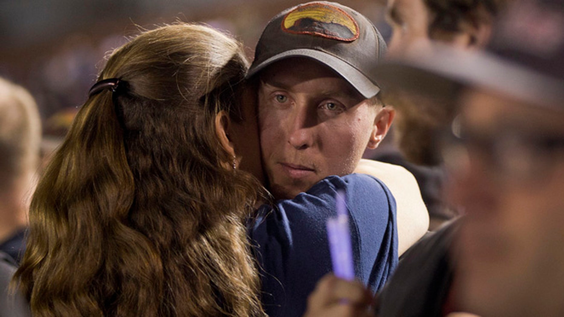 In this July 2, 2013 file photo, firefighter Brendan McDonough embraces a mourner near the end of a candlelight vigil in Prescott, Ariz. McDonough was the sole survivor of the 20-man Granite Mountain Hotshot Crew after an out-of-control blaze killed the 19 near Yarnell, Ariz. Investigators are set to release a report Saturday, Sept. 28, 2013, on the deaths of the 19 elite firefighters who became trapped by flames in a brush-choked canyon north of Phoenix.