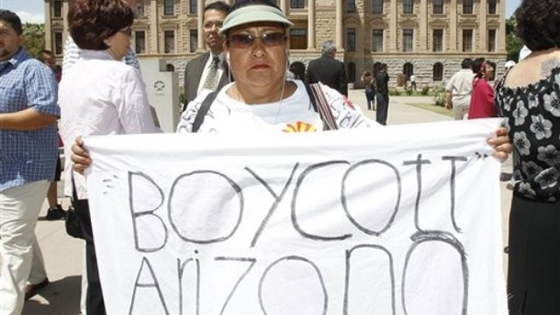 This April 29 file photo shows Josephine Nevarez, of Phoenix, holding a sign in protest of the Arizona immigration law at the Arizona Capitol in Phoenix. (AP Photo)
