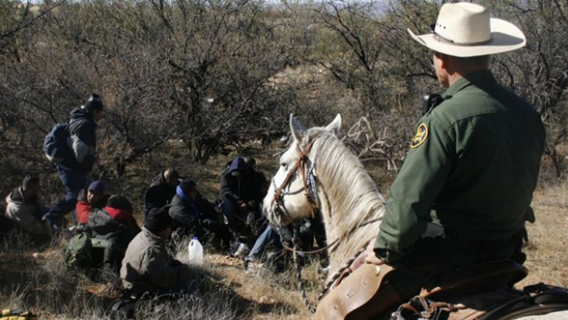 FILE: Jan. 9, 2008: A U.S. Border Patrol agent watches over a group of immigrants arrested after crossing illegally from Mexico through the Altar Valley in Arizona.