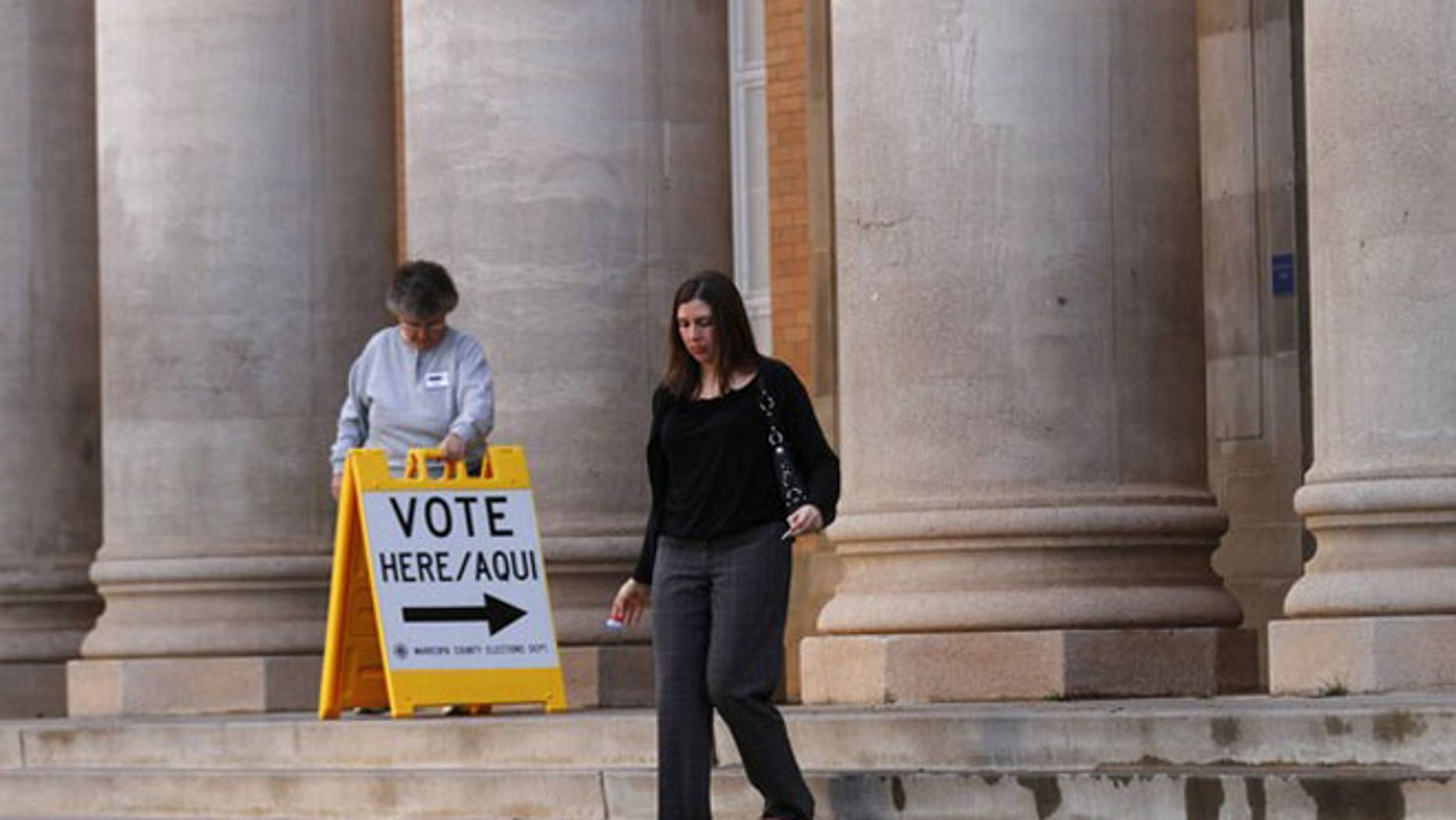 February 28, 2012: Sarah Moran leaves a polling station after voting as election-day volunteer Vicki Groff moves a vote sign at Kenilworth School in Phoenix, Arizona.