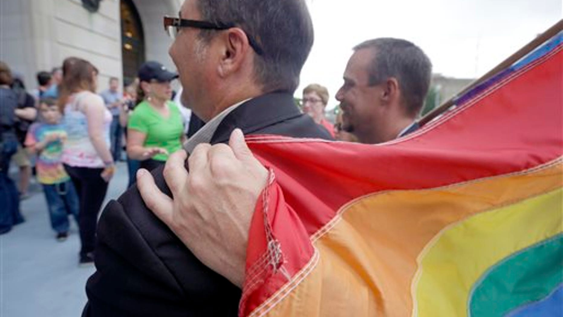 May 12, 2014: Shon DeArmon, right, puts his arm around his partner James Porter while holding a flag outside the Pulaski County Courthouse in Little Rock, Ark.