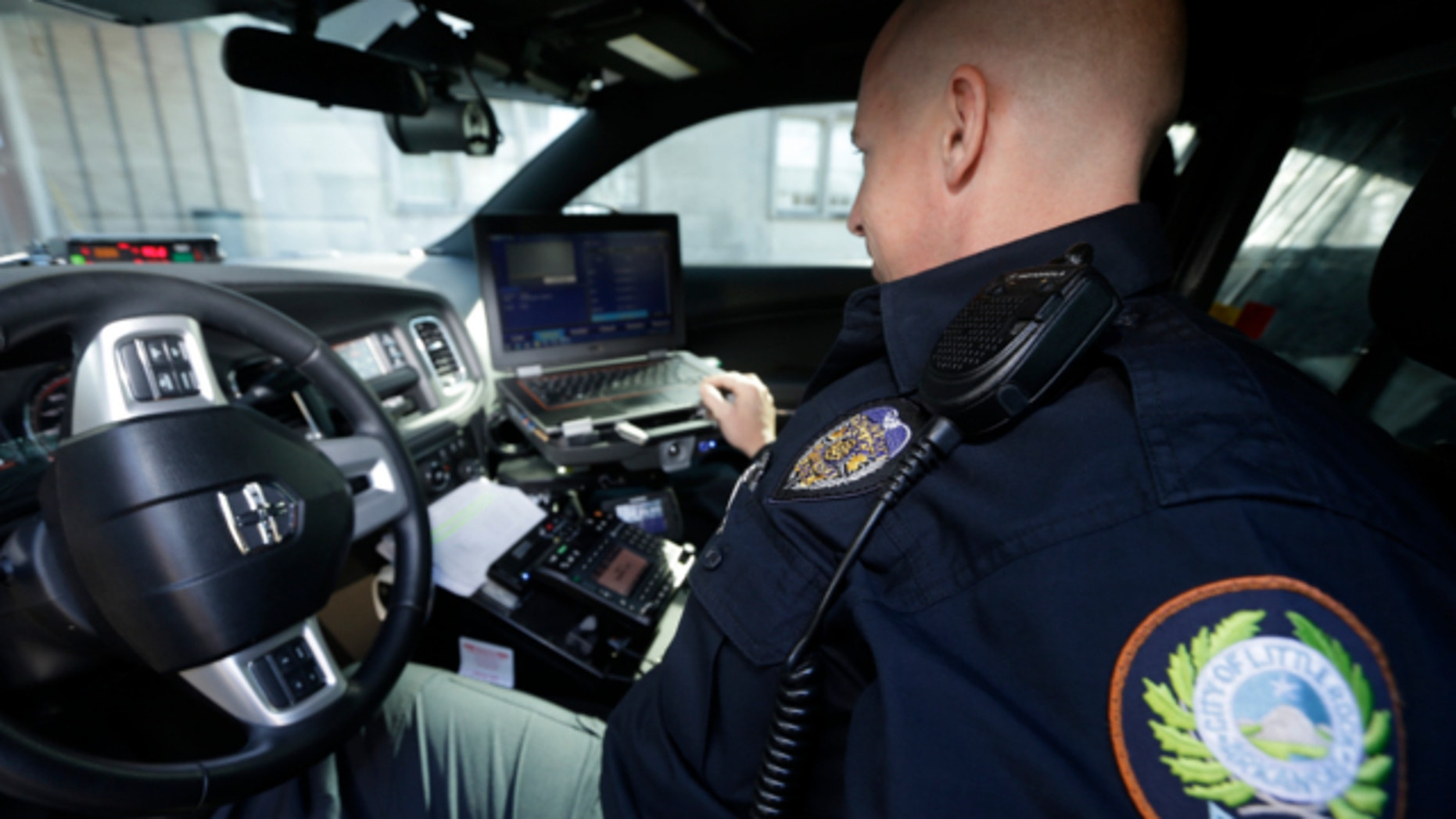 Jan. 16, 2013: Little Rock Police Officer Grant Humphries loos at a computer monitor connected to a camera mounted near the rear window of his patrol car in Little Rock, Ark.