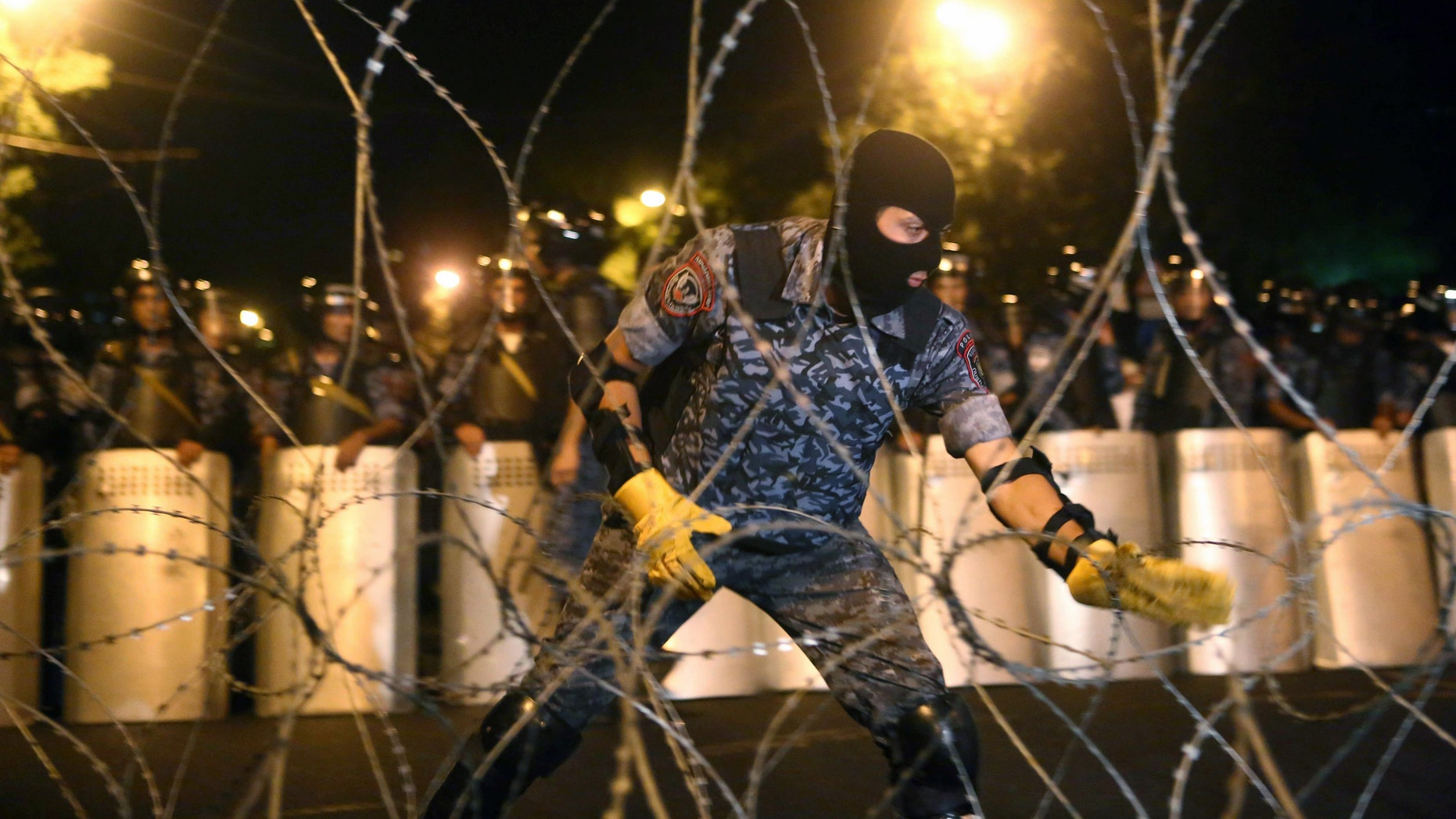 A riot police officer installs barbed wire during an anti-government march in Armenia.