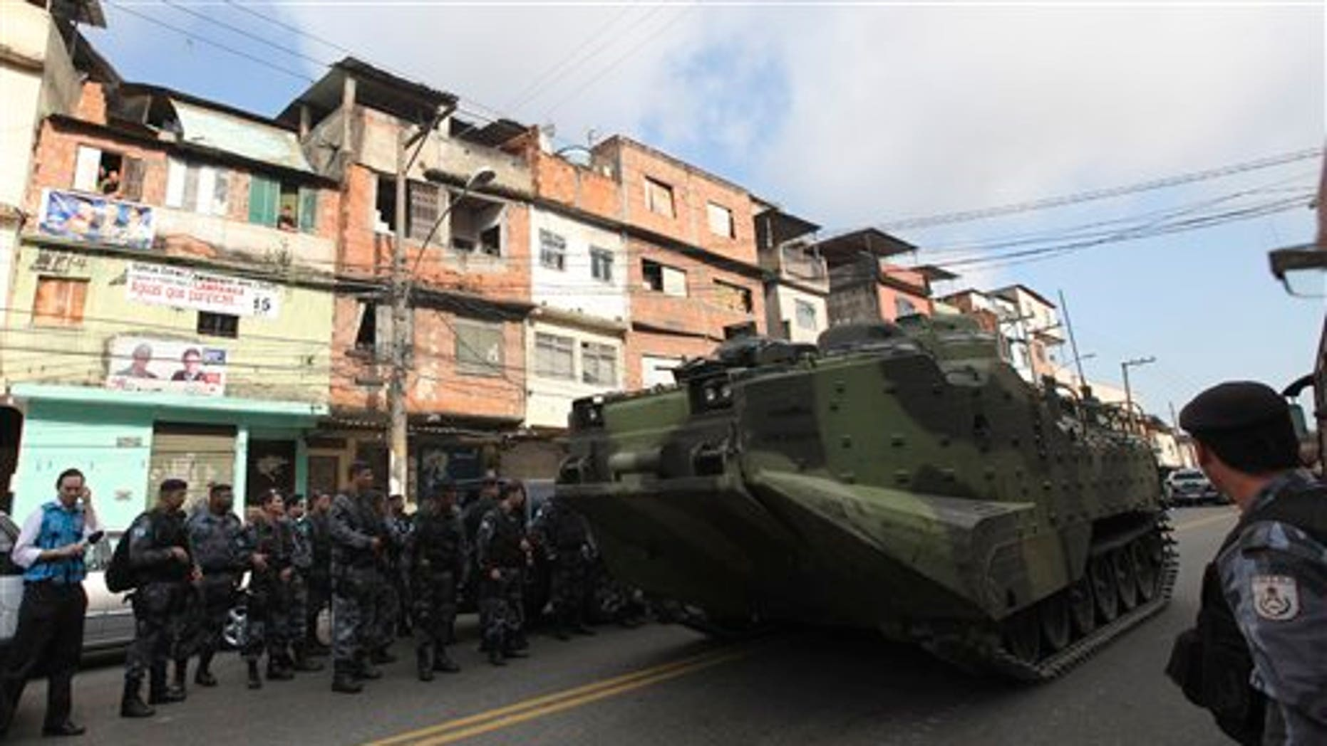 Soldiers stand next to an armored vehicle during a police operation against drug traffickers at the Complexo do Alemao slum in Rio de Janeiro, Brazil, Sunday, Nov. 28, 2010. Rio police backed by helicopters and armored vehicles, started invading a shantytown complex long held by traffickers on Sunday, slowly moving their way through small alleys amid heavy gunfire. (AP Photo/Andre Penner)