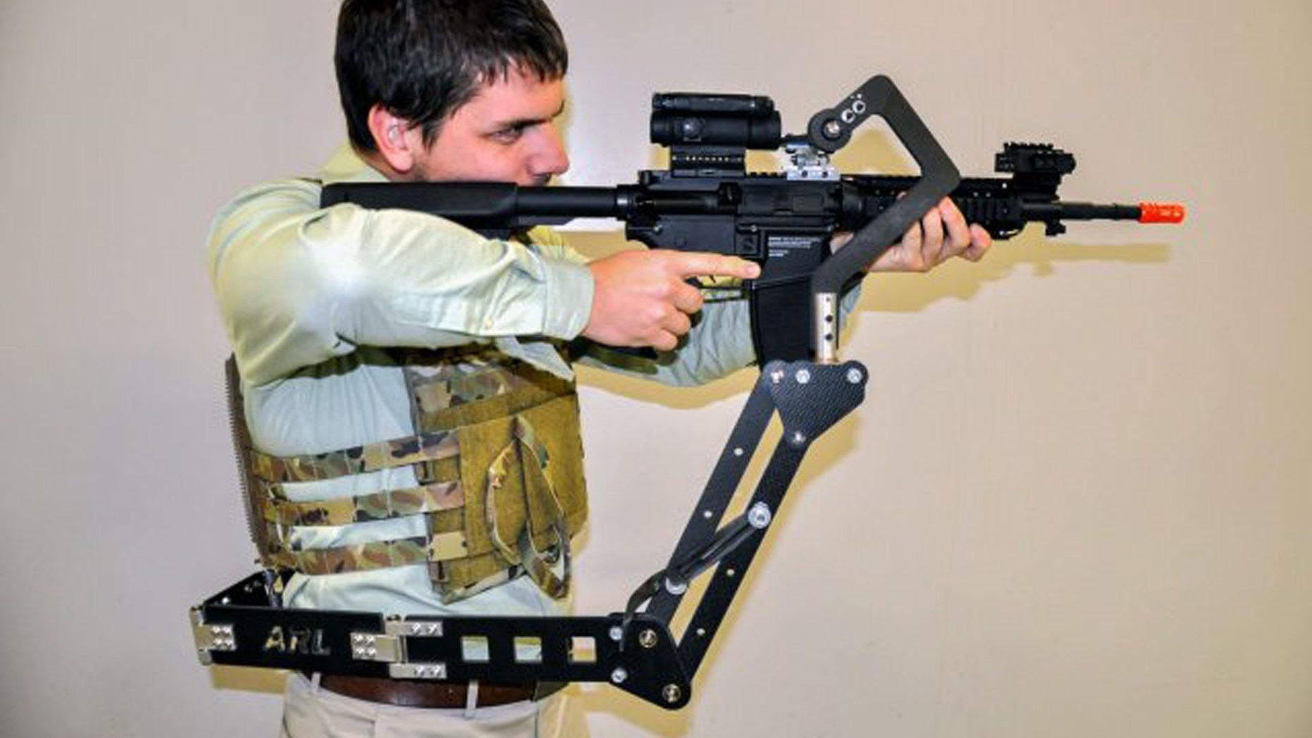 """The Army Research Laboratory is developing a """"third arm"""" passive mechanical appendage that could lessen Soldier burden and increase lethality. Weighing less than 4 pounds, the device attaches to a Soldier's protective vest and holds their weapon, putting less weight on their arms and freeing up their hands to do other tasks. (Photo Credit: U.S. Army)"""