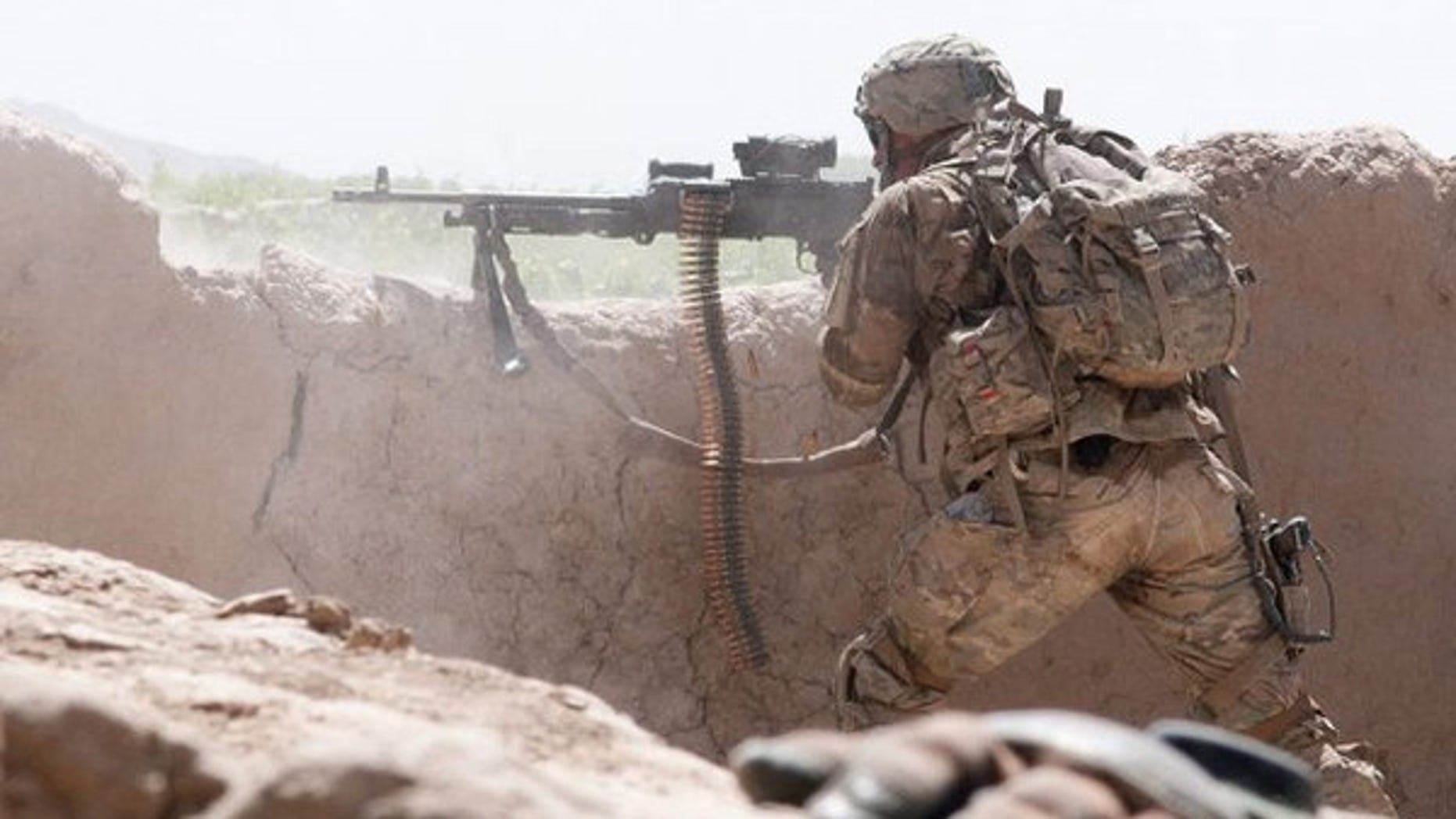 A paratrooper with the 82nd Airborne Division's 1st Brigade Combat Team fires an M240B medium machine gun at insurgent forces in southern Ghazni Province, Afghanistan on June 15, 2012.