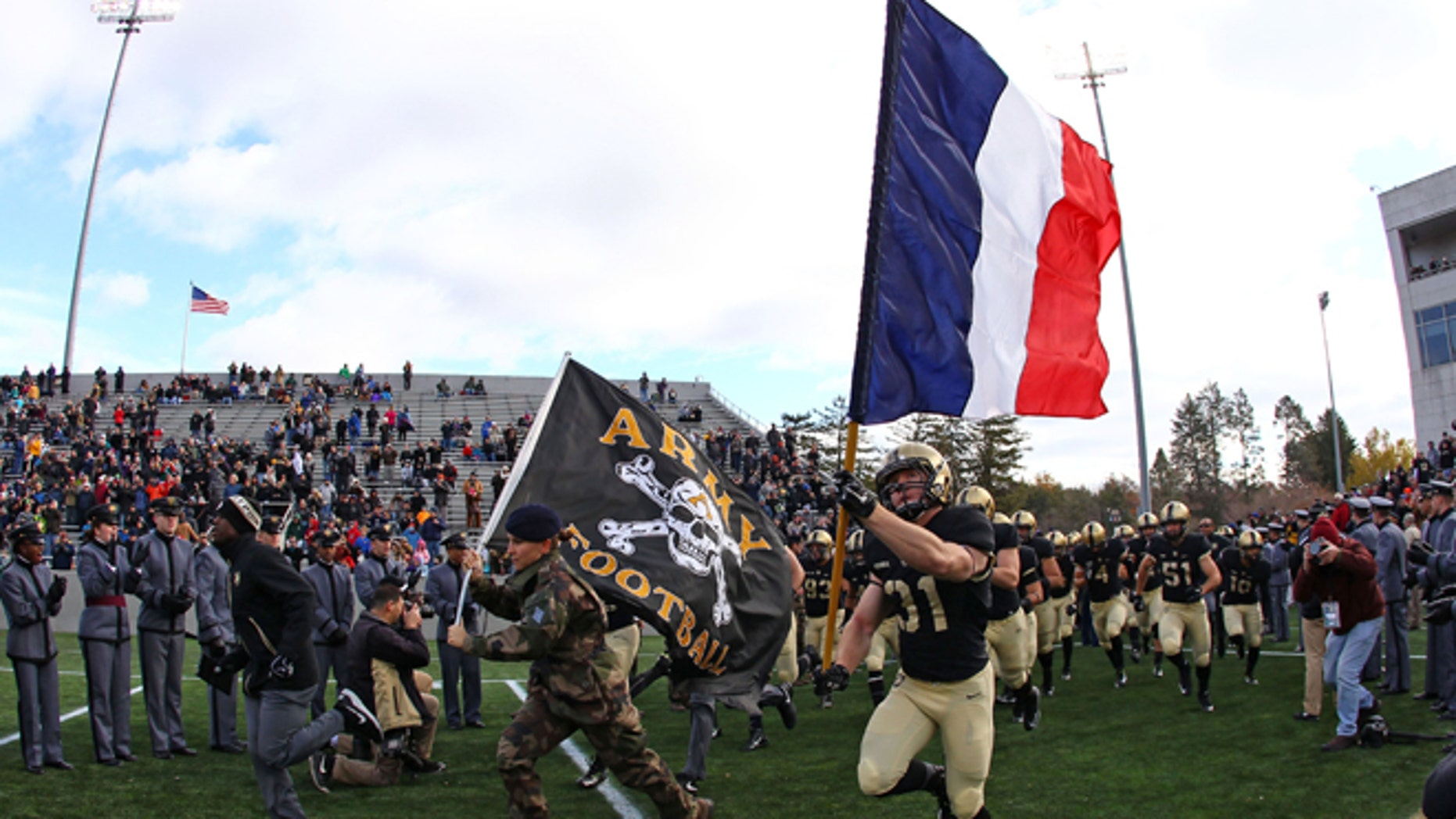 Nov 14, 2015; West Point, NY, USA; Army Black Knights defensive back Caleb McNeill (31) carries a French flag on to the field alongside a French exchange cadet before a game against the Tulane Green Wave at Michie Stadium.