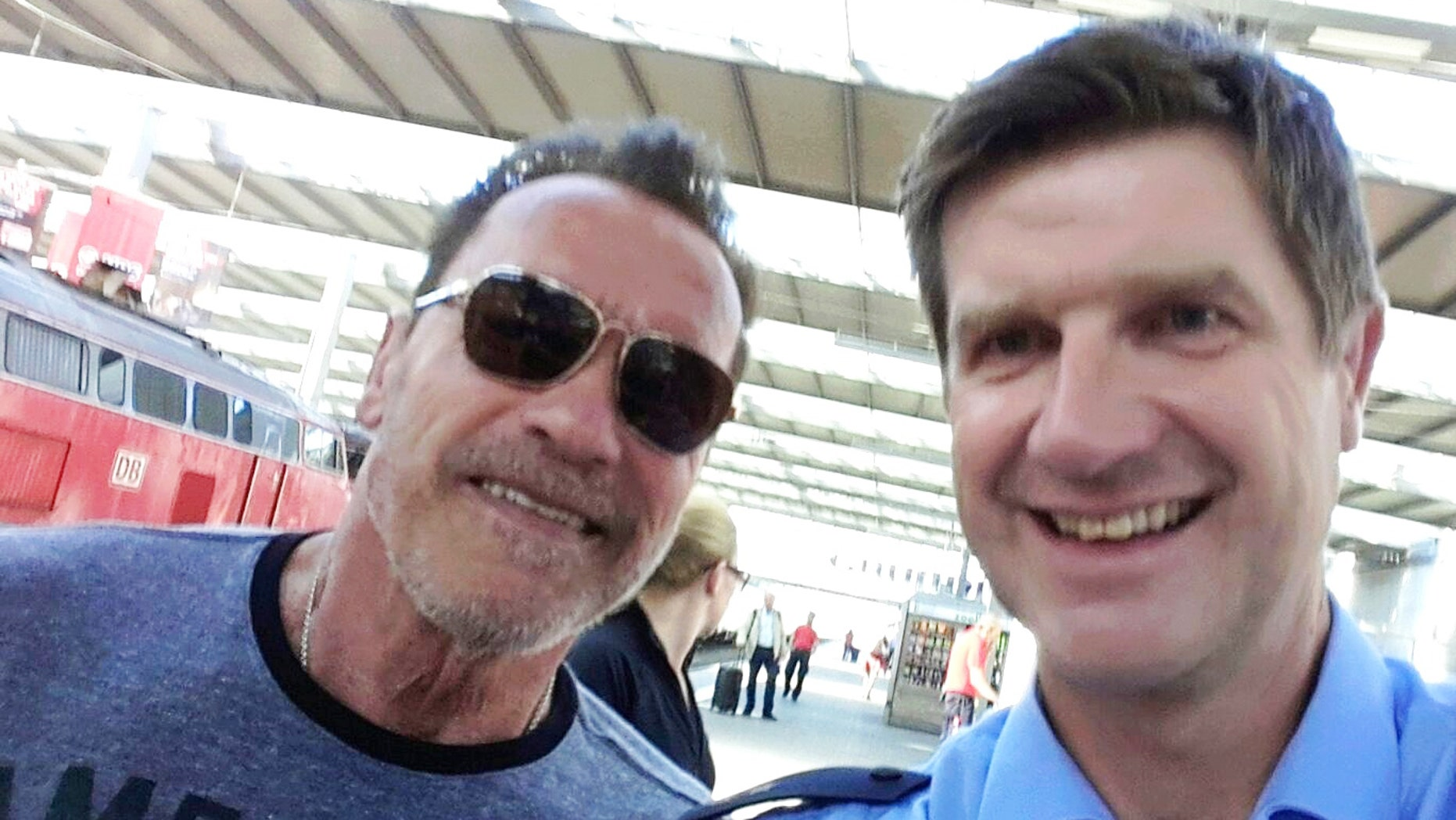 Arnold Schwarzenegger poses with Munich police officer Stefan Schmitt after being stopped for cycling too fast in a Munich train station.