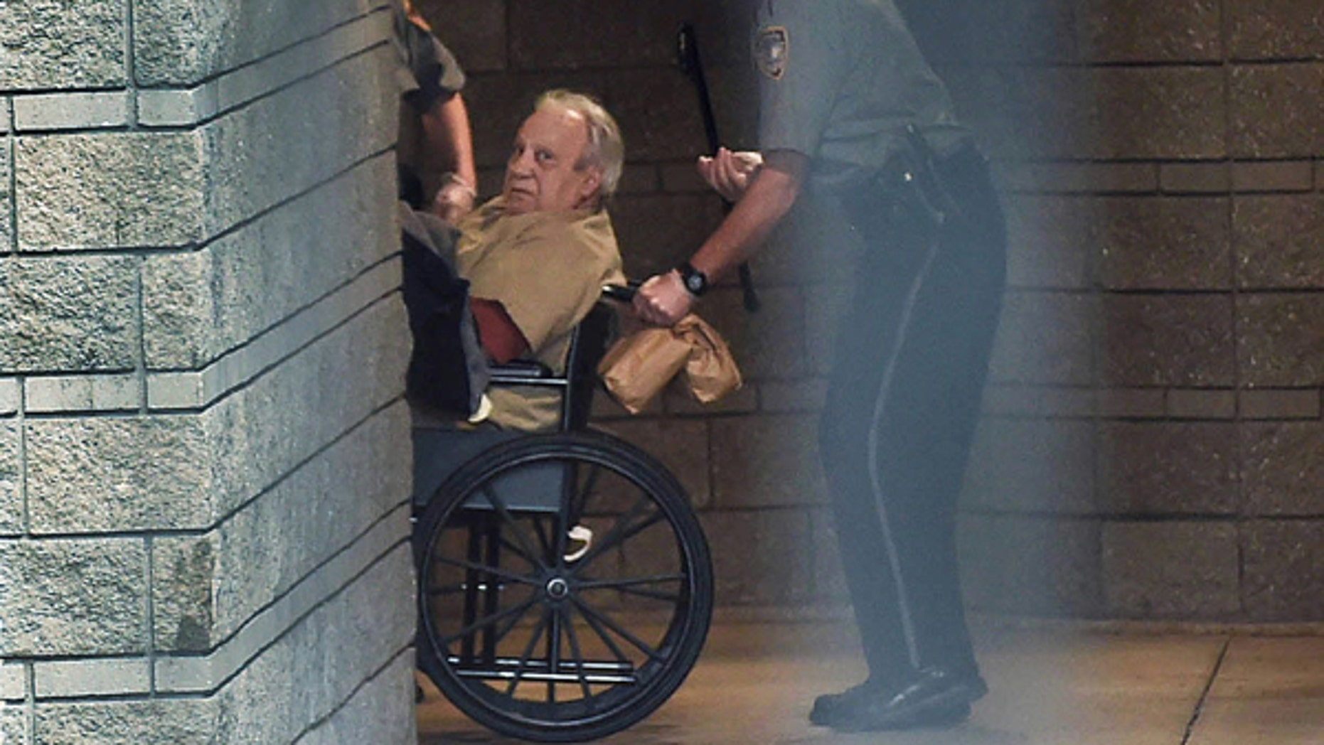 Robert Gentile is brought into the federal courthouse in a wheelchair for a hearing in Hartford, Conn.