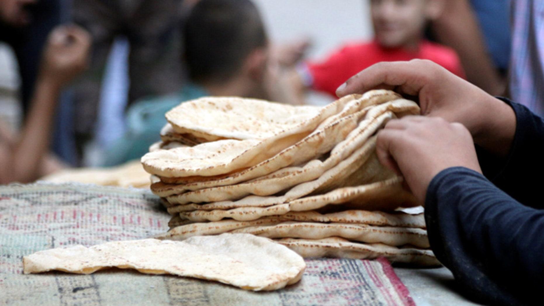 A boy arranges bread in the rebel held al-Shaar neighbourhood of Aleppo