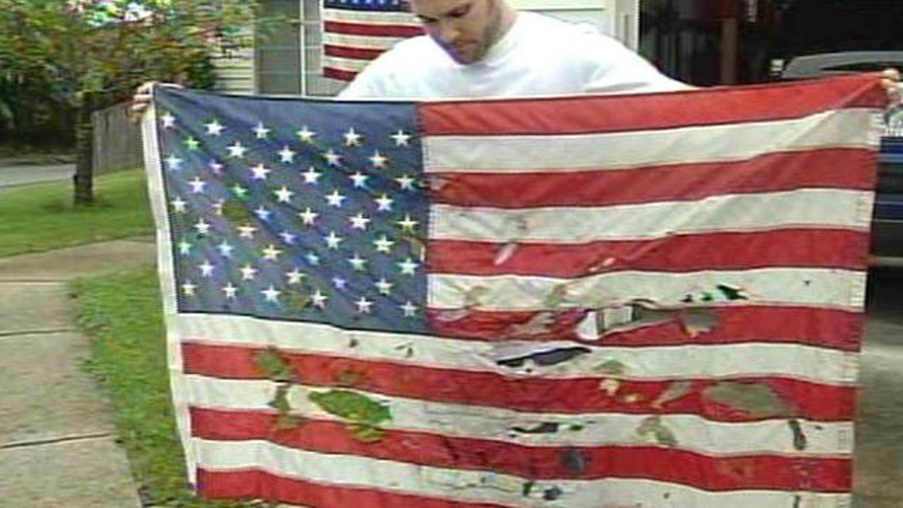 Christian Ashby, of Portland, Ore., holds an American flag that was vandalized outside of his home sometime late Saturday or early Sunday.