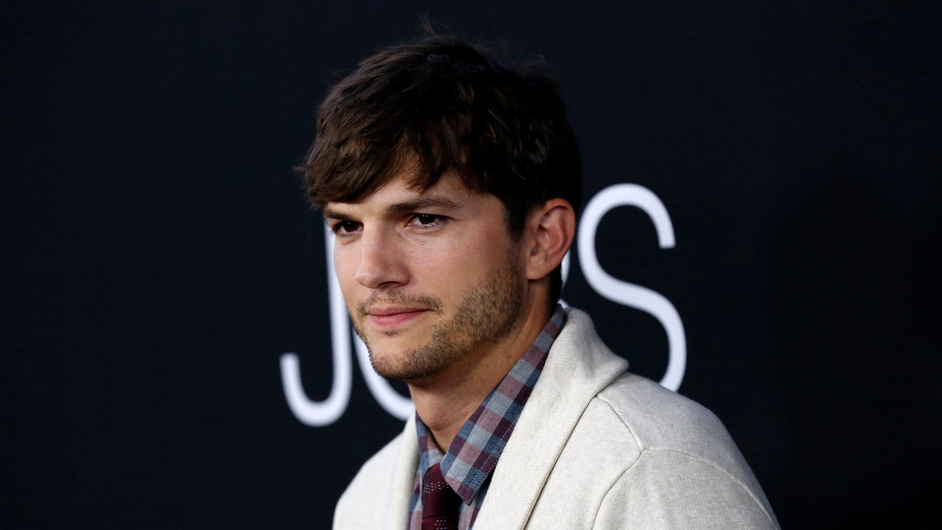 """August 13, 2013. Cast member Ashton Kutcher poses at the premiere of """"Jobs,"""" in Los Angeles, California."""
