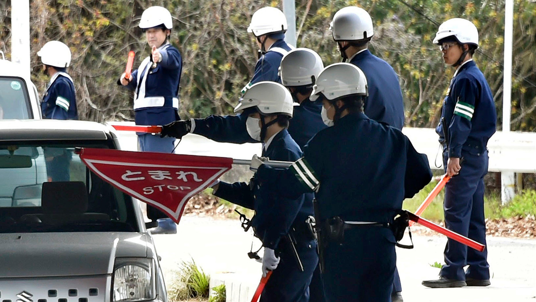 In this April 11, 2018, photo, police officers inspect cars at a checkpoint in Onomichi, Hiroshima prefecture.