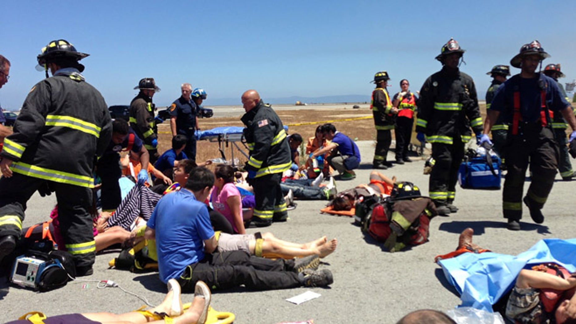 In this Saturday, July 6, 2013, photo provided by passenger Benjamin Levy, passengers from Asiana Airlines flight 214 are treated by first responders on the tarmac just moments after the plane crashed at the San Francisco International Airport in San Francisco. The flight crashed upon landing, and two of the 307 passengers aboard were killed.