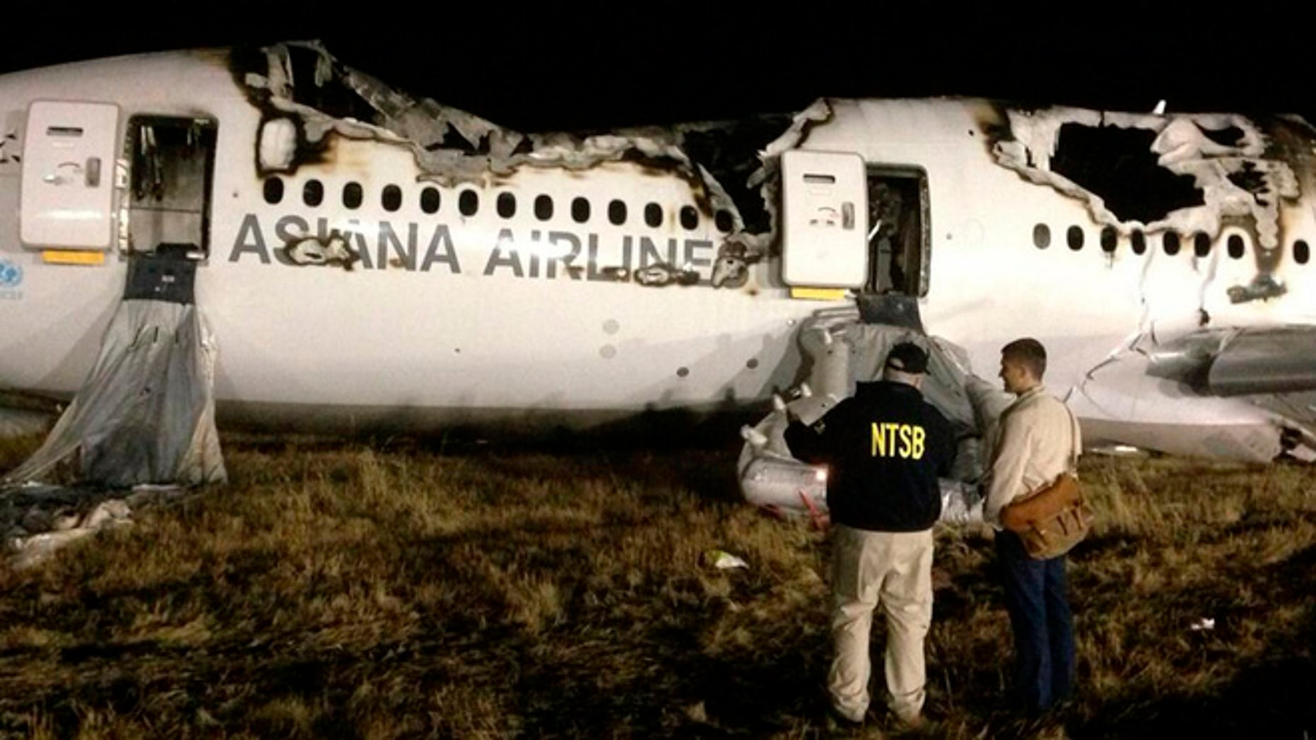 National Transportation Safety Board (NTSB) investigators conduct first site assessment of the wreckage of Asiana Airlines Flight 214, at San Francisco International Airport in San Francisco, California in this July 6, 2013 handout photo.