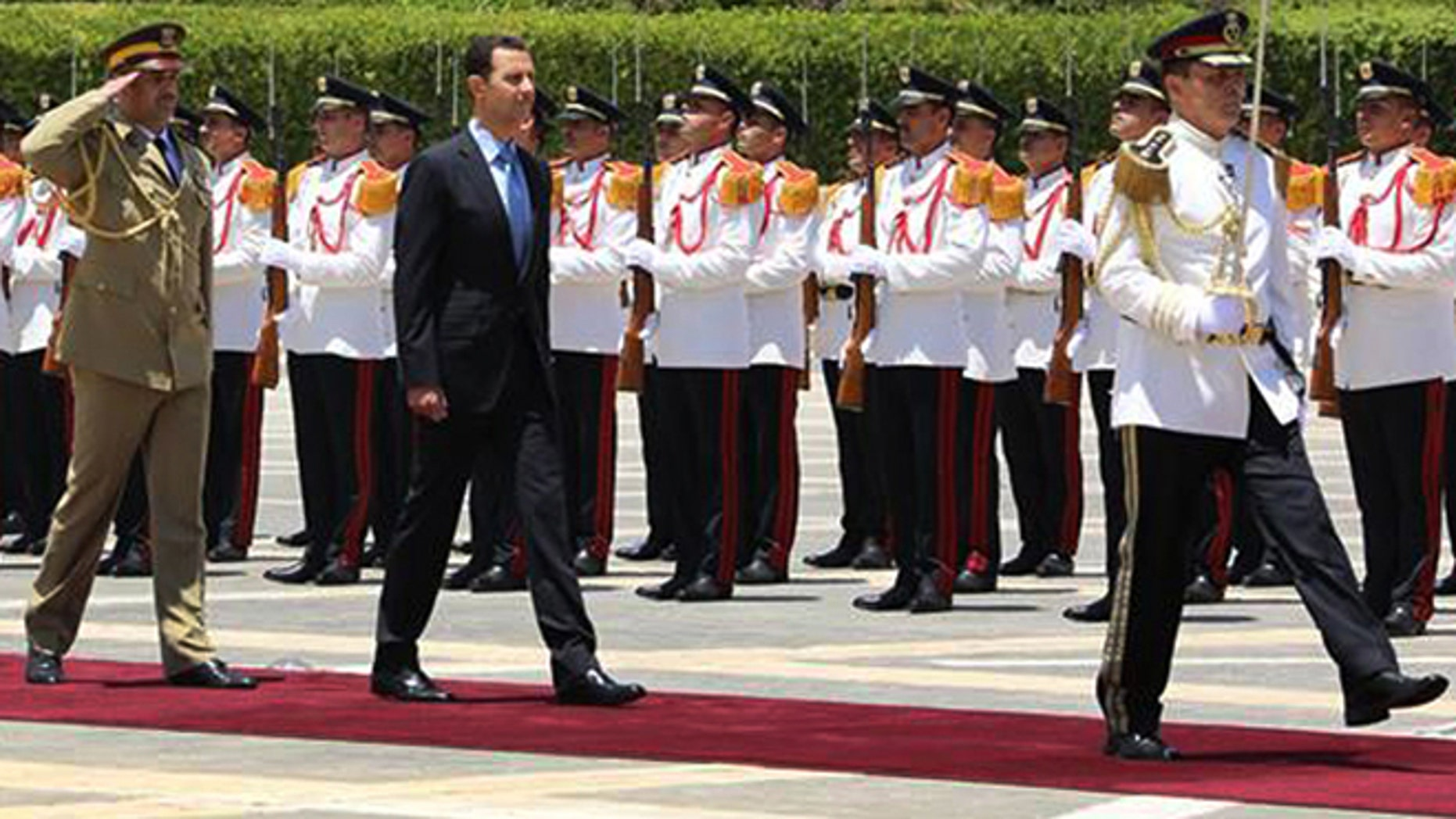 July 16, 2014: In this photo released by the Syrian official news agency SANA, Syria's President Bashar Assad, center, reviews the honor guard upon his arrival at the presidential palace to take the oath of office for his third, seven-year term, in Damascus, Syria.