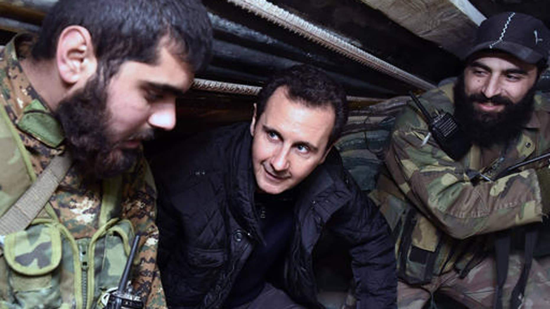 Syrian President Bashar Assad, center, speaks with Syrian troops during his visit to the front line in the eastern Damascus district of Jobar, Syria, on Dec. 31, 2014. (AP Photo)