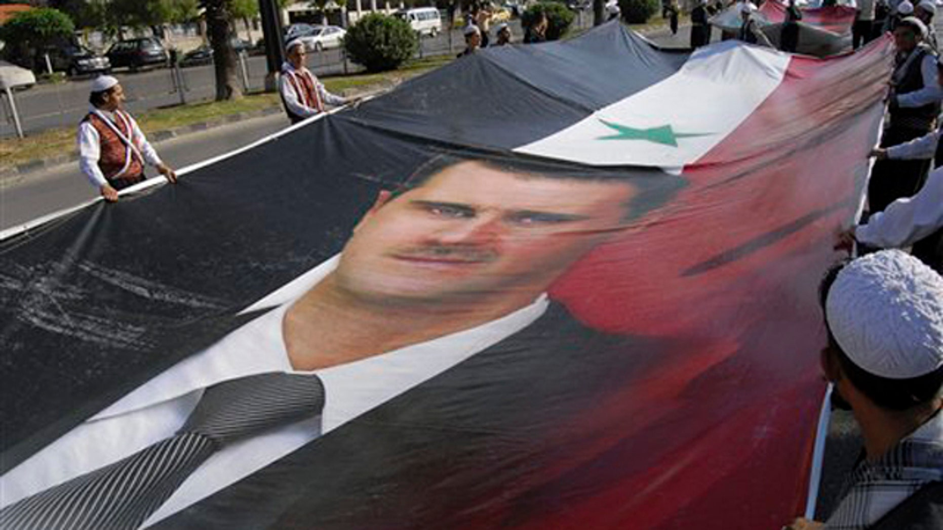 Supporters of Syrian President Bashar Assad carry a huge portrait of Assad as they march during a demonstration in his support in Damascus, Syria, June 8.