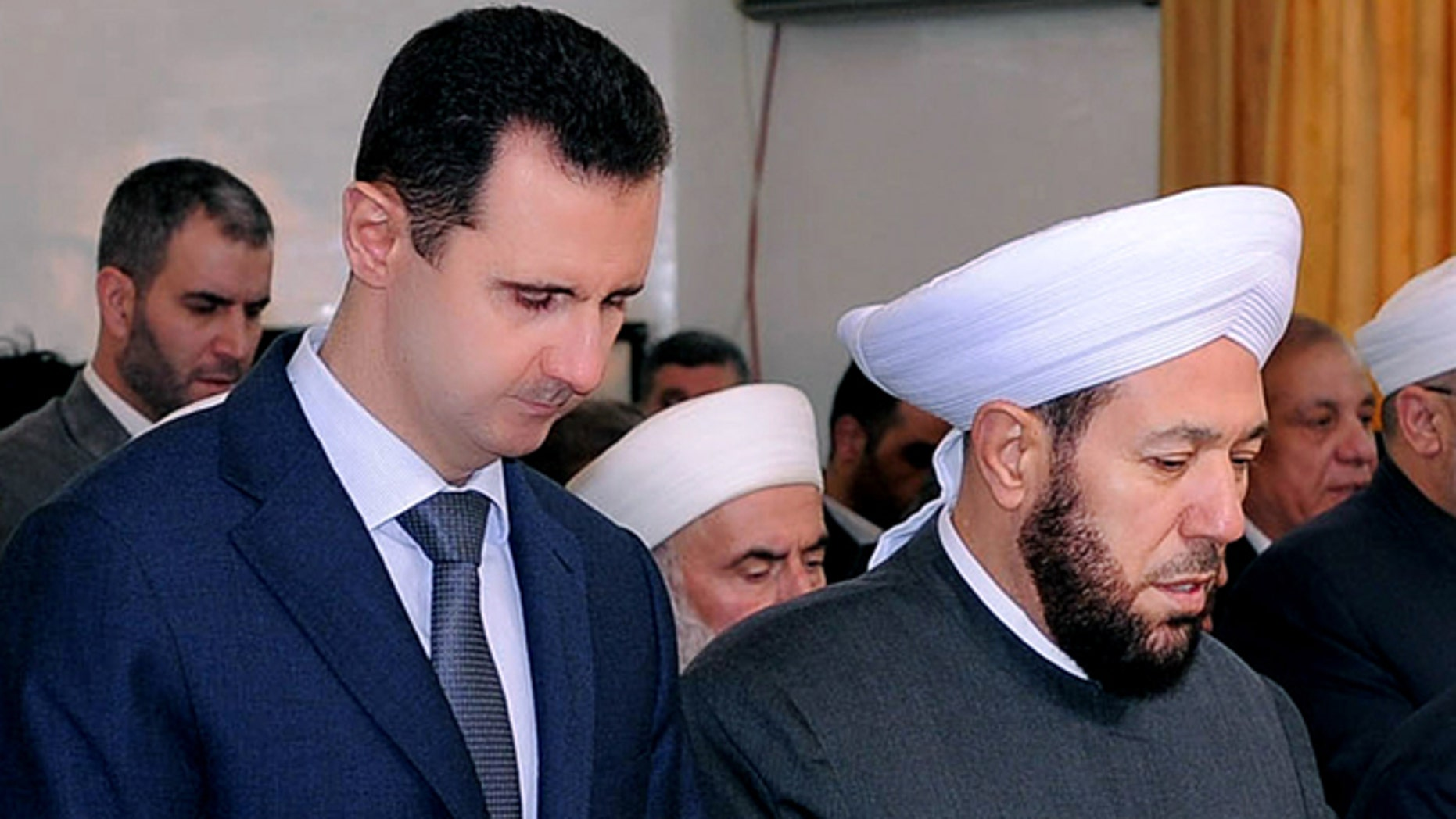 Feb. 5, 2012: In this photo released by the Syrian official news agency SANA, Syrian President Bashar Assad, left, prays next to the Syrian grand mufti Ahmad Hassoun, right, during a ceremony marking the birth of Islam's Prophet Mohammad, at al-Rawda mosque, in Damascus, Syria. Hassoun's appeal for men to join the army raises the question of whether President Bashar Assad is running out of soldiers and prompts a pro-government newspaper to declare the military can battle insurgents for years to come.