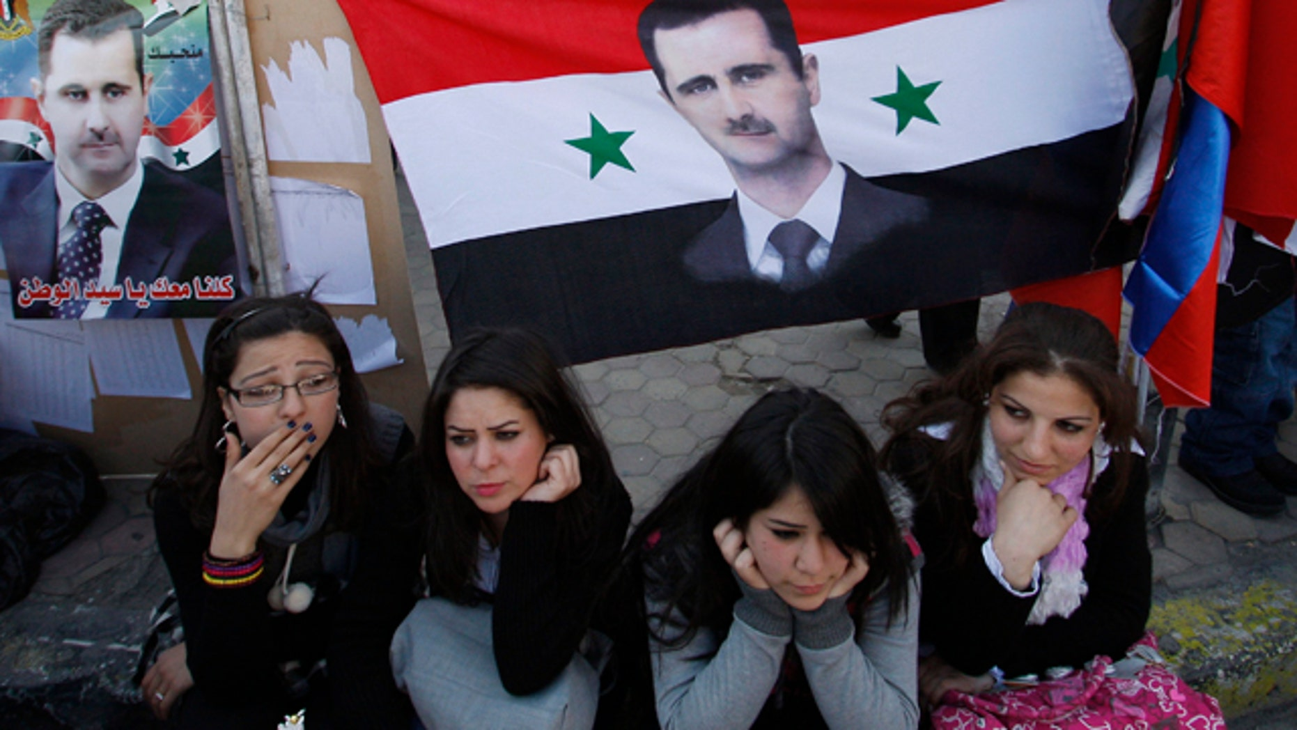 Feb. 26: Syrian women sit under a Syrian flag with a portrait of Syrian President Bashar Assad, outside a polling station during a referendum on the new constitution, in Damascus.