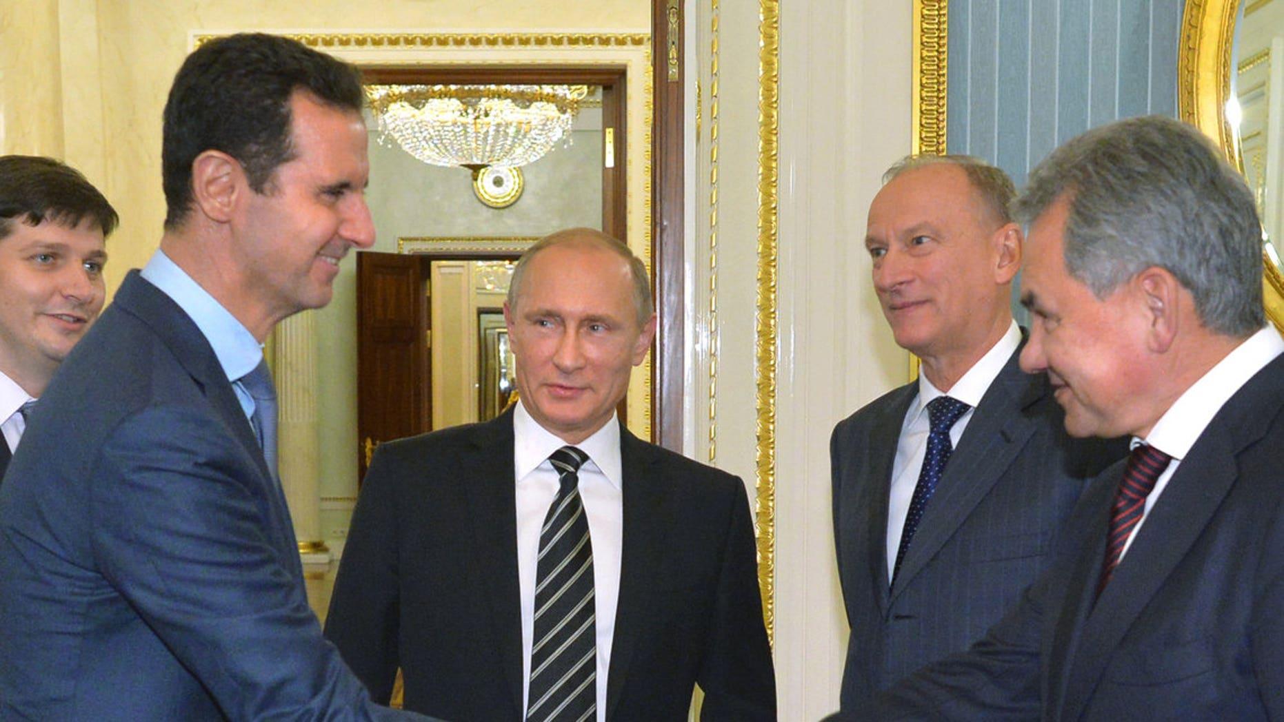 Assad, second left, shakes hand with Shoigu as Russian President Vladimir Putin, center, looks on, in October 2015.