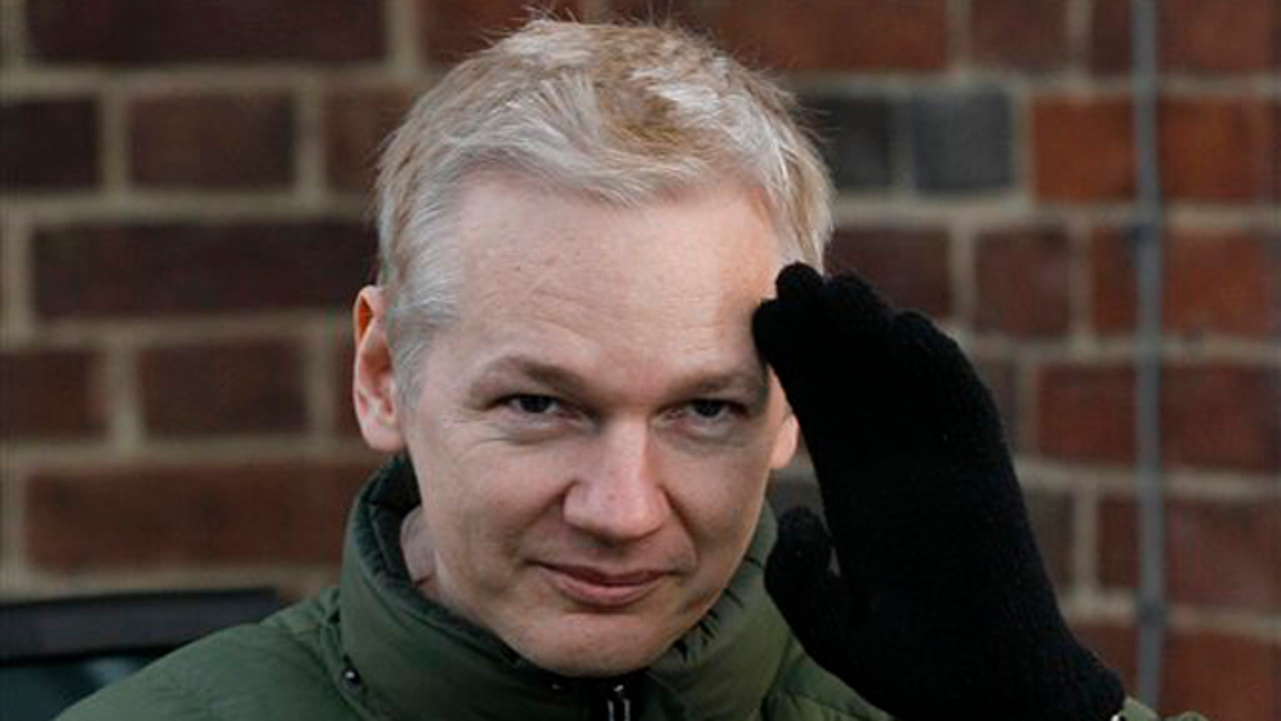 WikiLeaks founder Julian Assange gestures as he gets back into a car at Beccles Police Station in Suffolk, England, on Dec. 17.