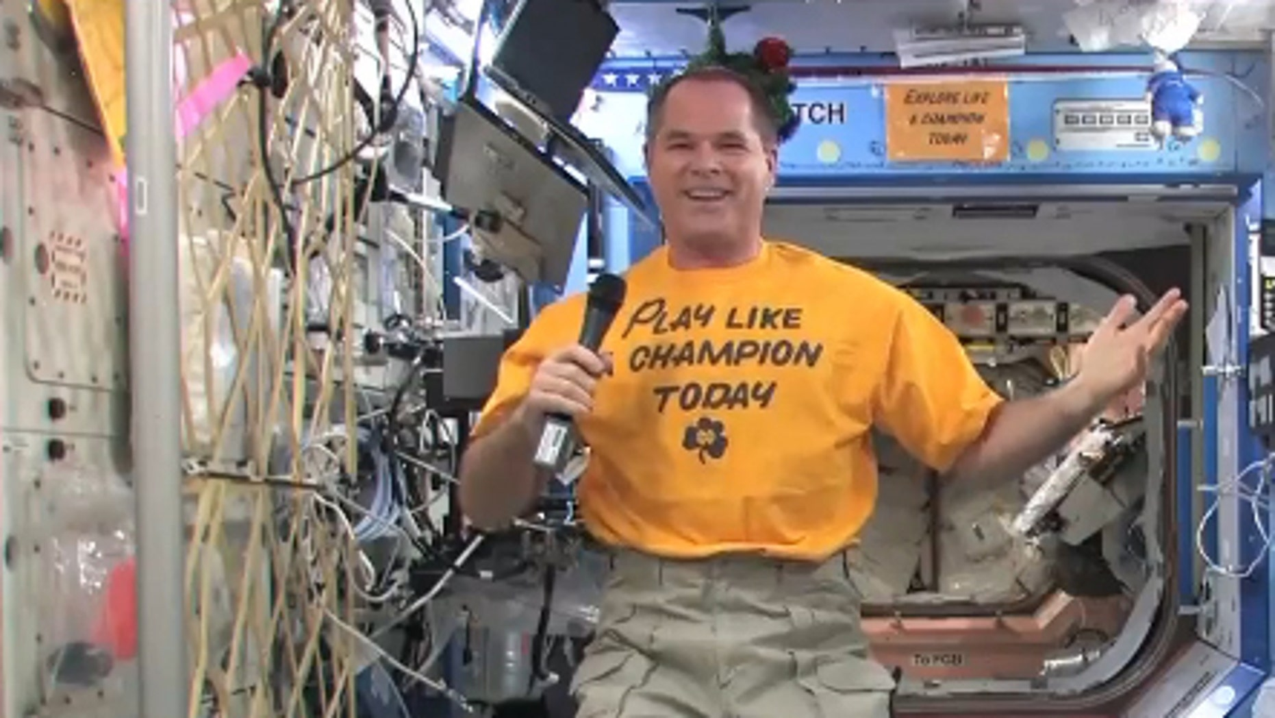 """NASA astronaut Kevin Ford smiles while wearing his Notre Dame """"Play Like a Champion Today"""" shirt on Dec. 26 to support the college's BCS Championship Game against Alabama on Jan. 7, 2013. Ford is the commander of Expedition 34 aboard the Intern"""