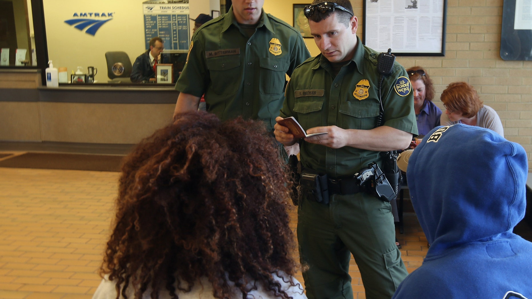 DEPEW, NY - JUNE 05:  U.S. Border Patrol agents check passenger identifications at a train station on June 5, 2013 in Depew, New York. The agents set up a 24 hour check of transportation hubs in and around Buffalo. They said they received intelligence of undocumented immigrants passing through the area. The Border Patrol also monitors cross border traffic along the northern border between the United States and Canada.  (Photo by John Moore/Getty Images)