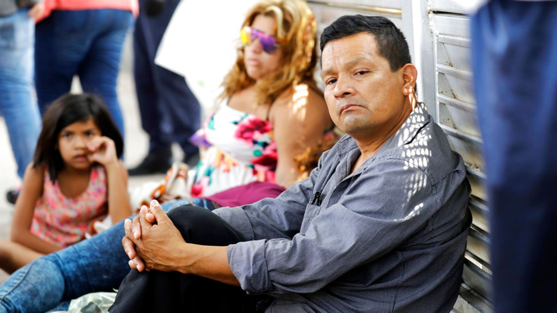 Ruben Prado, right, an immigrant from Guatemala seeking asylum in the United States, waits on the Gateway International Bridge along with a family from Honduras, in Matamoros, Mexico on Sunday, June 24, 2018. Prado arrived at the bridge today after traveling for 20 days. (AP Photo/David J. Phillip)
