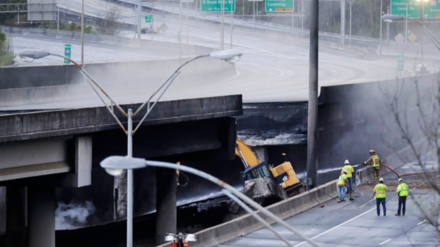 Crews work on a section of an overpass that collapsed from a large fire on Interstate 85 in Atlanta, Friday, March 31, 2017.